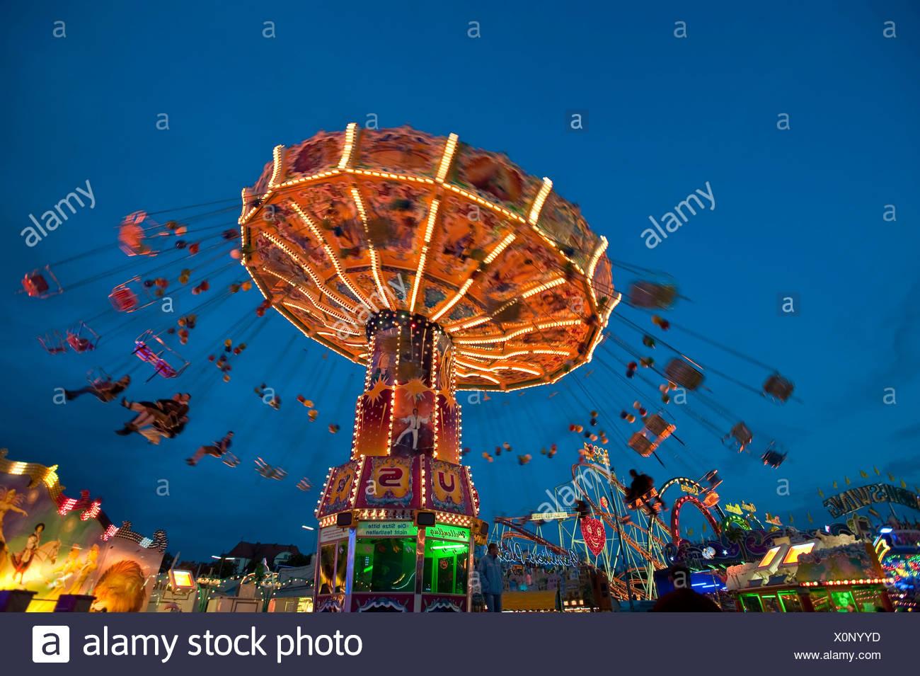 Illuminated Chairoplane at dusk, Oktoberfest festival, Munich, Bavaria, Germany Stock Photo