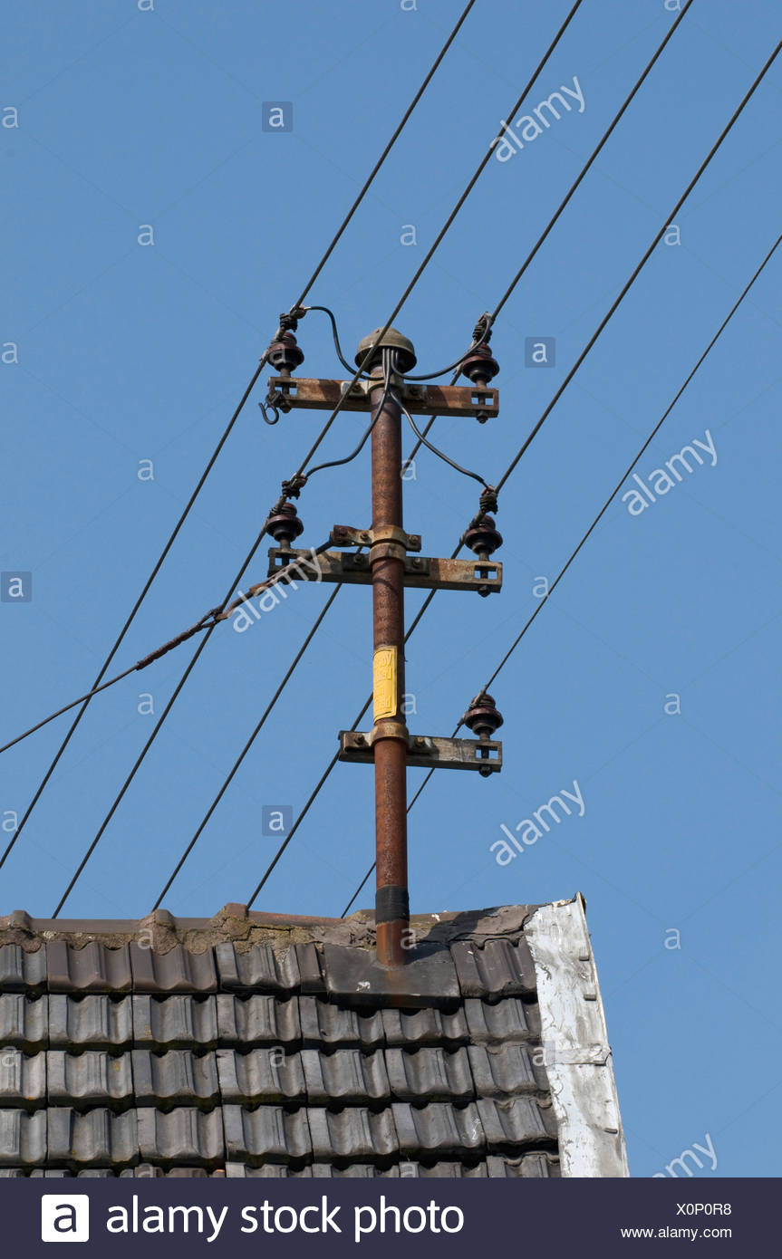 Old domestic overhead power lines with ceramic insulators on roof - Stock Image