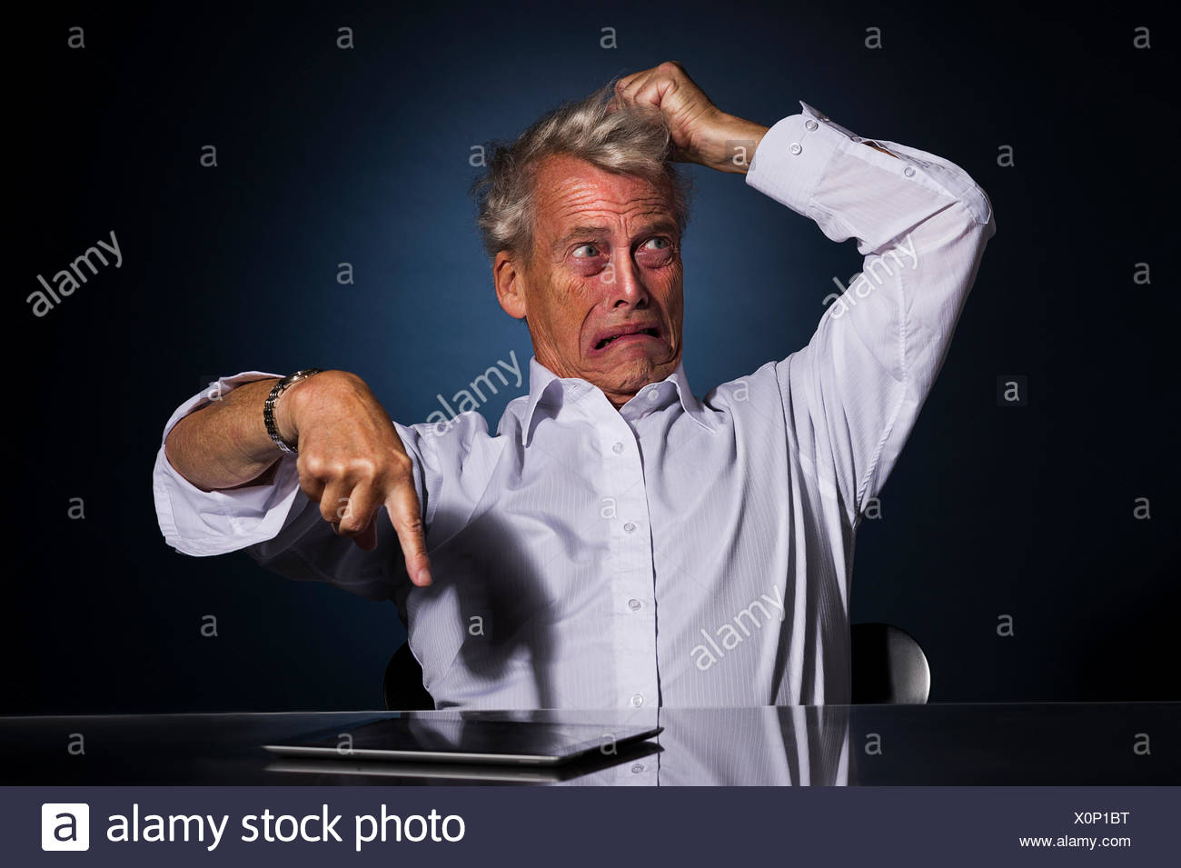 Upset frustrated senior man pointing at his tablet - Stock Image