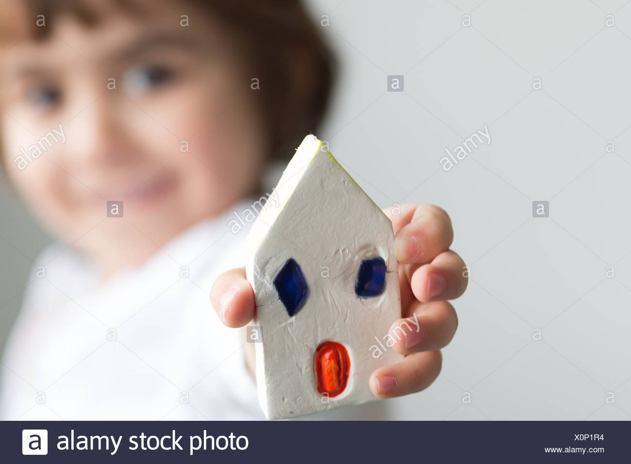 Boy showing off his handmade house - Stock Image