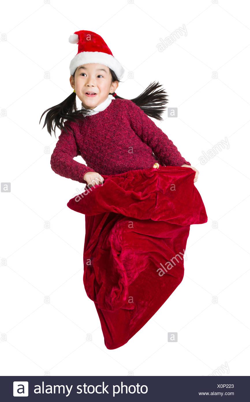 Happy girl jumping in large Santa bag - Stock Image