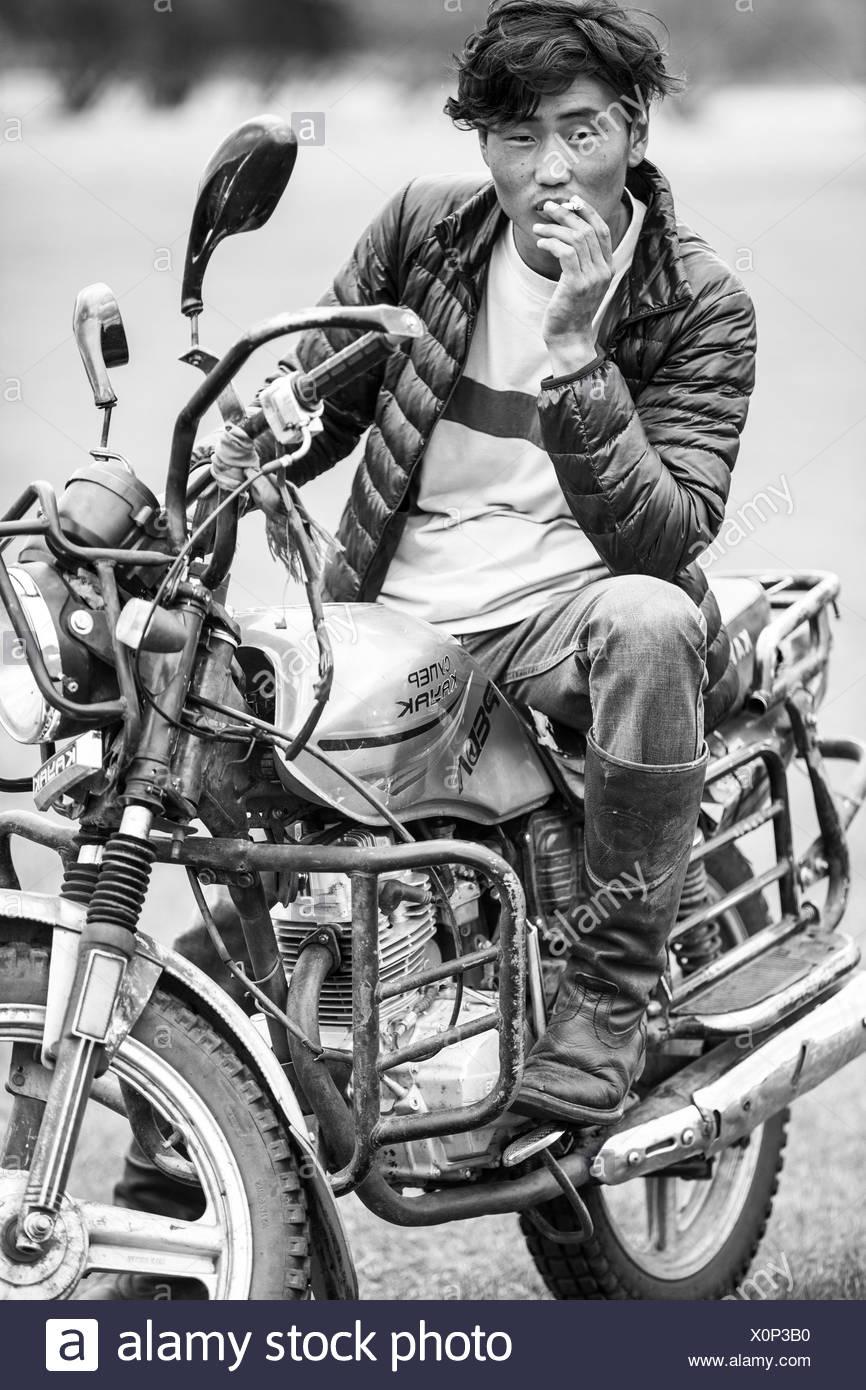 Portrait of Mongol cowboy sitting on motorcycle, Bulgan, Central Mongolia, Mongolia - Stock Image