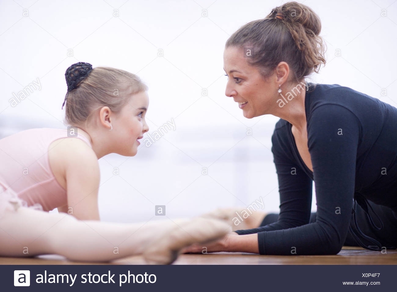 Teacher and young ballerina practicing floor stretch - Stock Image