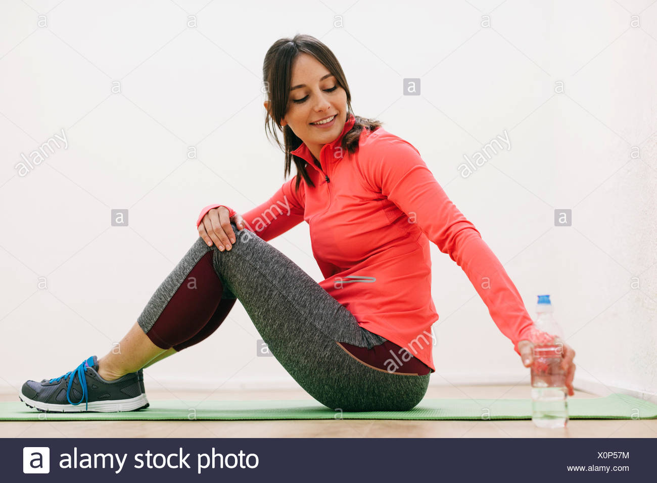 Young woman wearing tracksuit having a rest - Stock Image