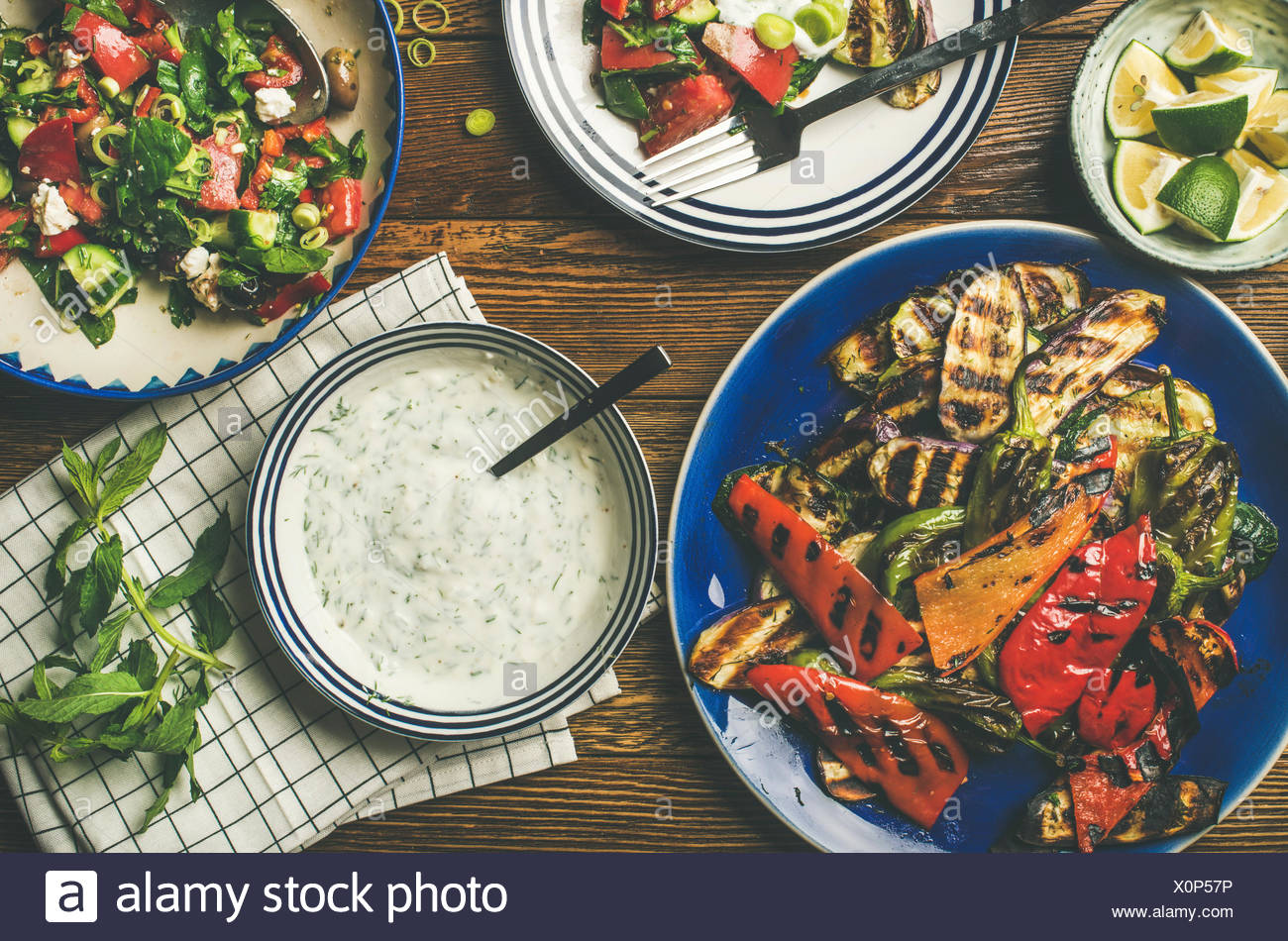 Flat-lay of healthy dinner table setting. Green salad, grilled vegetables with yogurt and garlic sauce, lime slices water over wooden background, top  - Stock Image