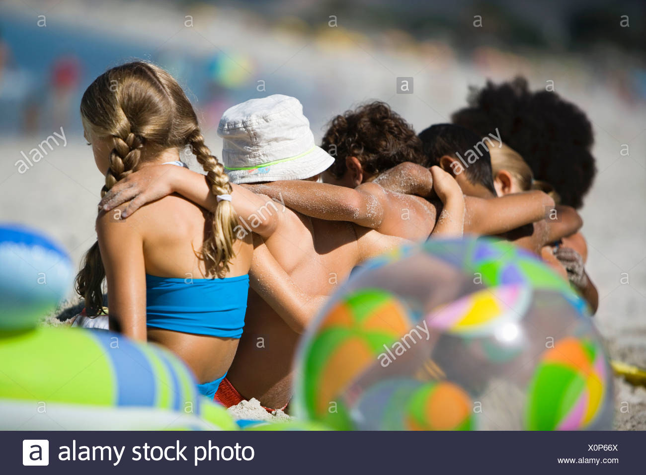 Children 4 9 sitting in line on beach rear view differential focus - Stock Image