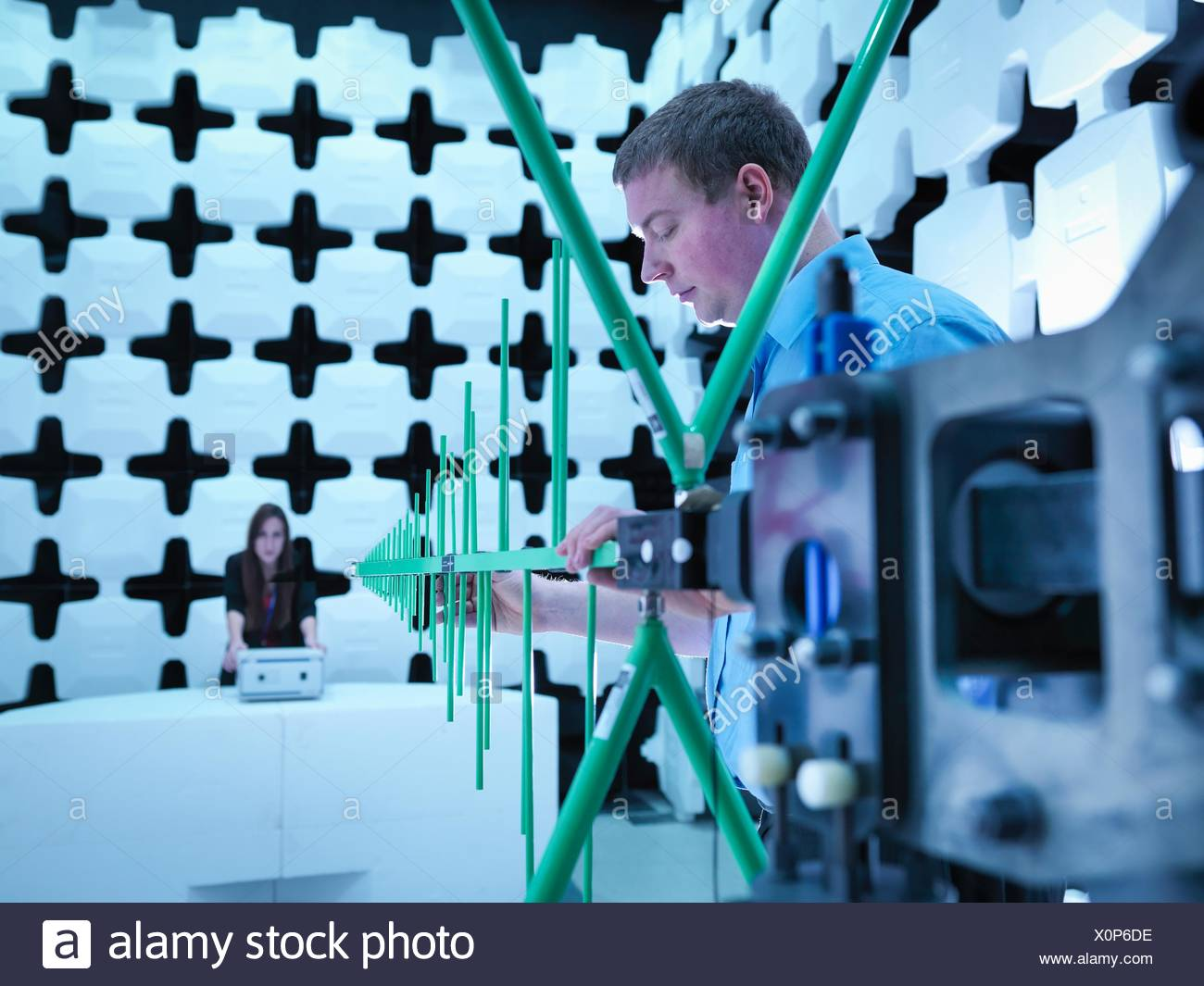 Engineers checking a bilog antenna for electromagnetic compatibility (EMC) radiated immunity testing in a semi anechoic chamber relative to the electronic equipment under test (EUT) - Stock Image