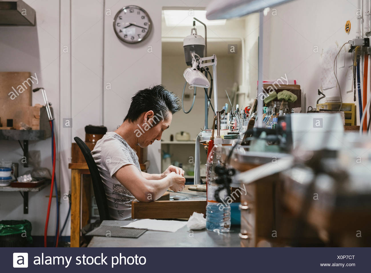 Male jeweller working at workbench - Stock Image