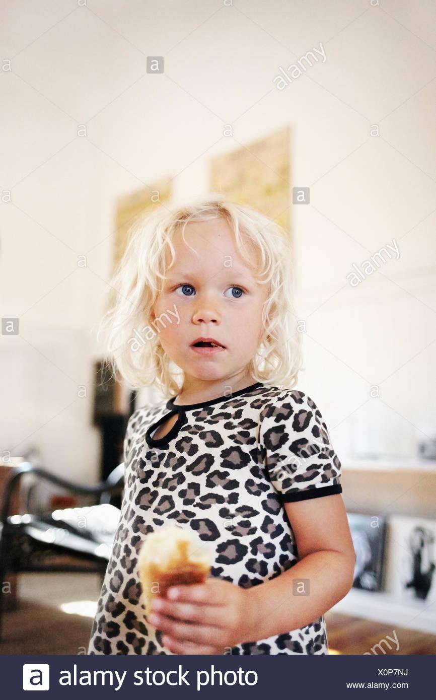 Portrait of blond girl (4-5) eating sweet bun - Stock Image