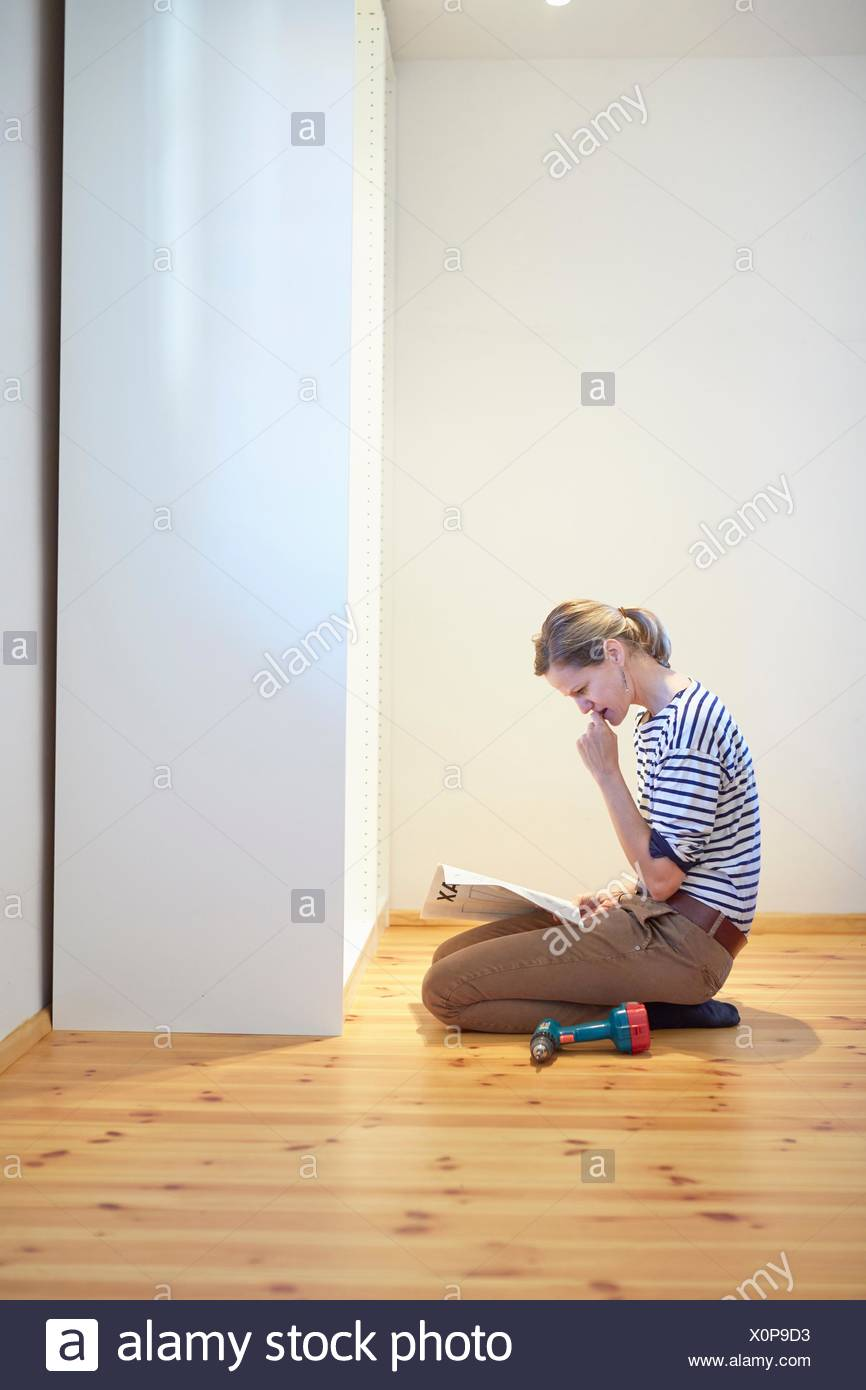 Mature woman kneeling and reading instruction manual for flatpack closet - Stock Image