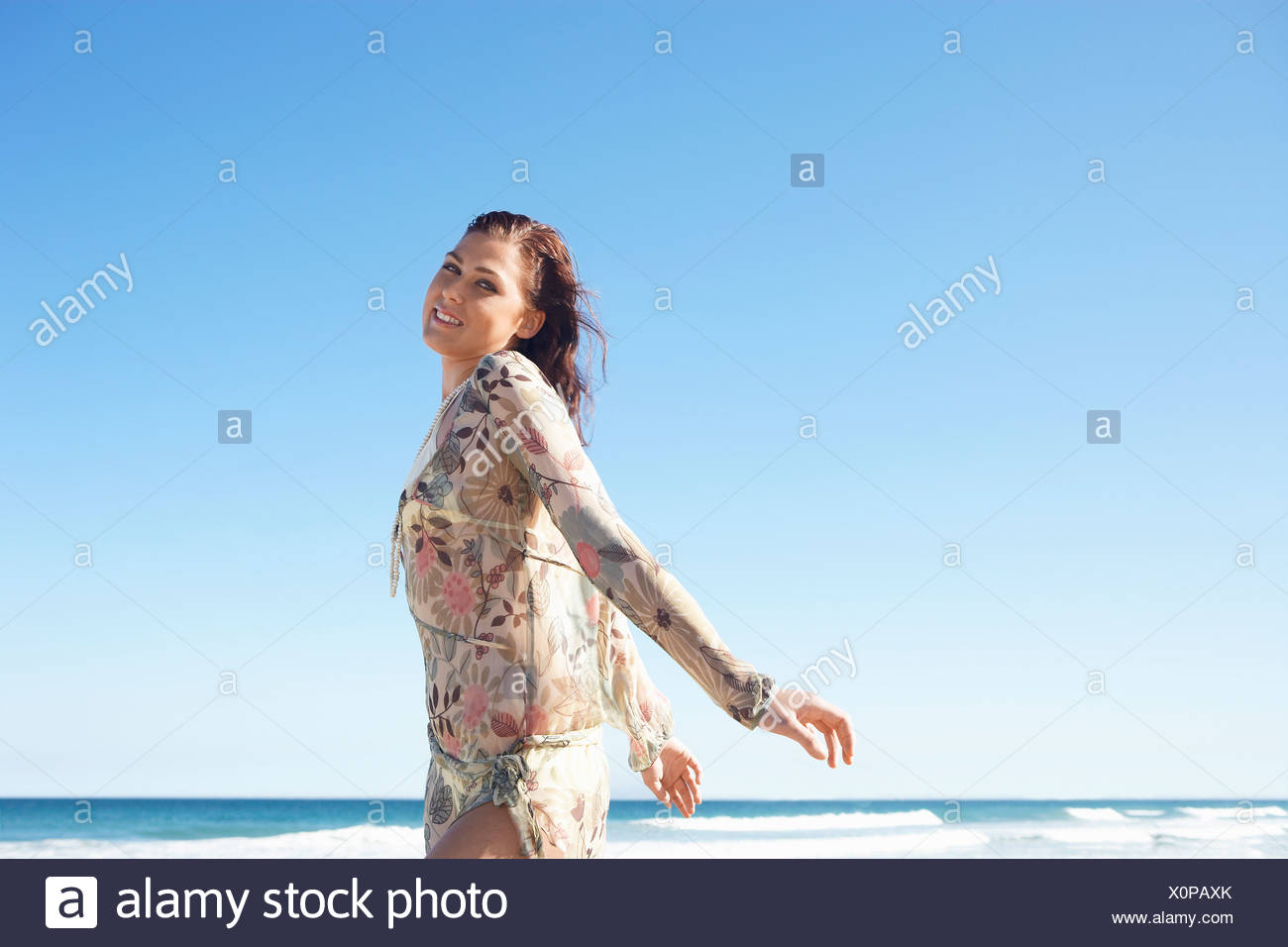 Young woman posing by sea, half-length - Stock Image