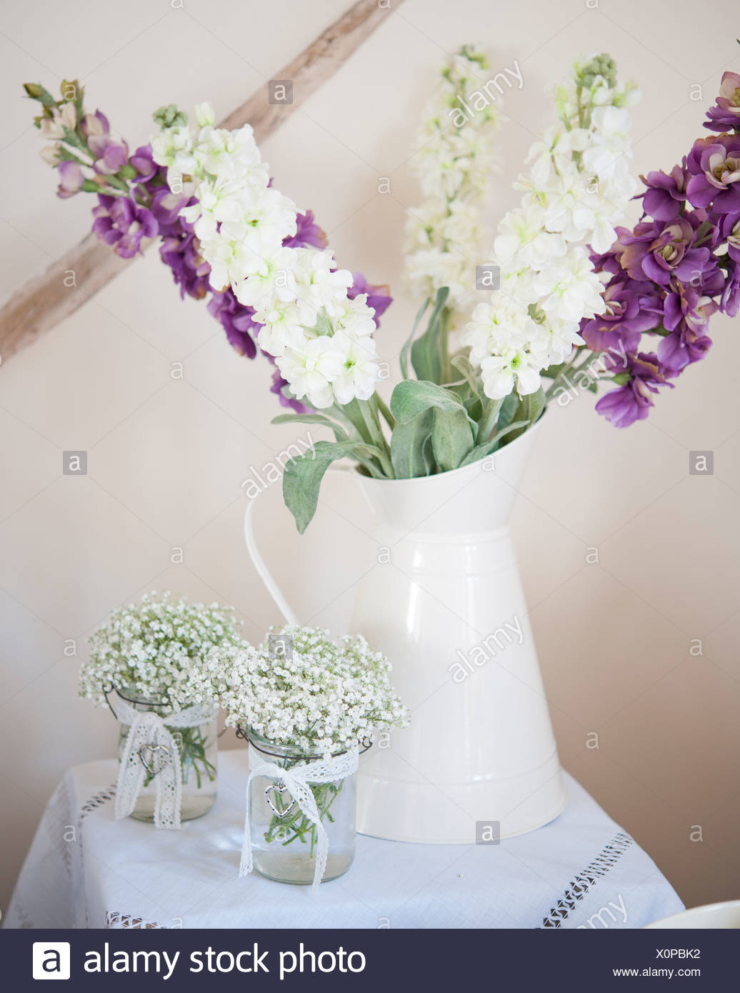 A jug of purple and white flowers with two small vases of white flowers & A jug of purple and white flowers with two small vases of white ...