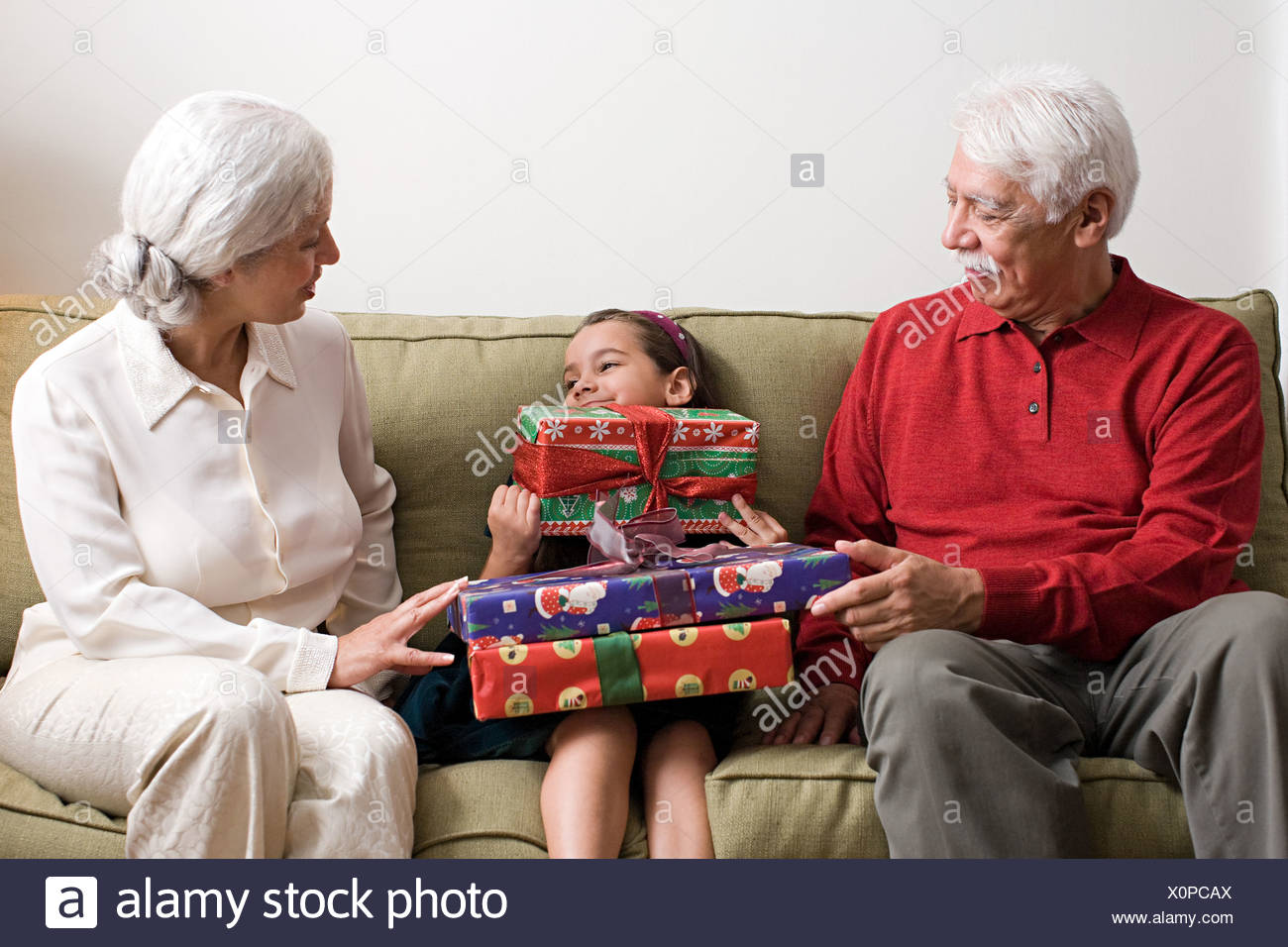 Grandparents and their granddaughter with gifts - Stock Image