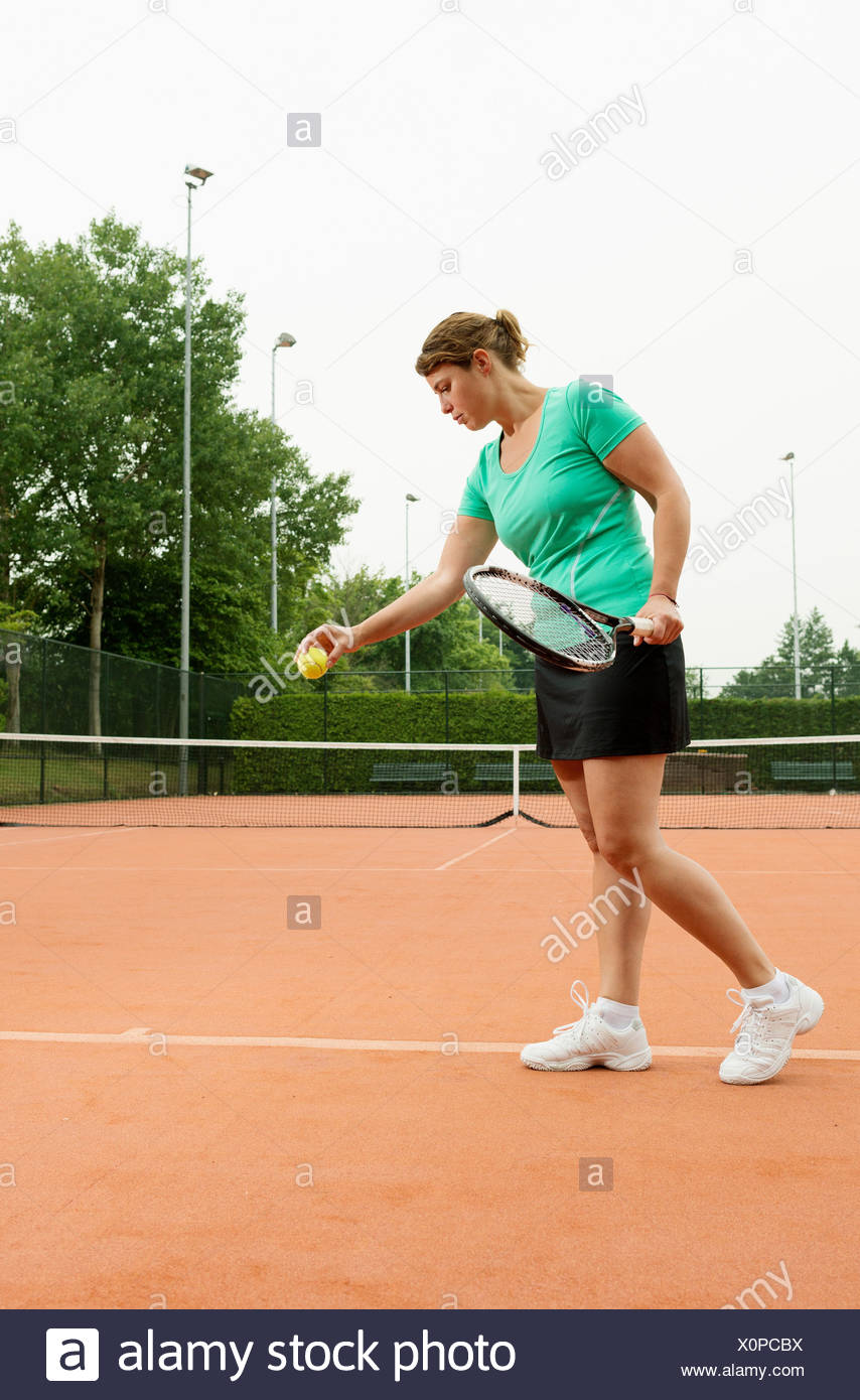 Woman preparing to serve tennis ball - Stock Image