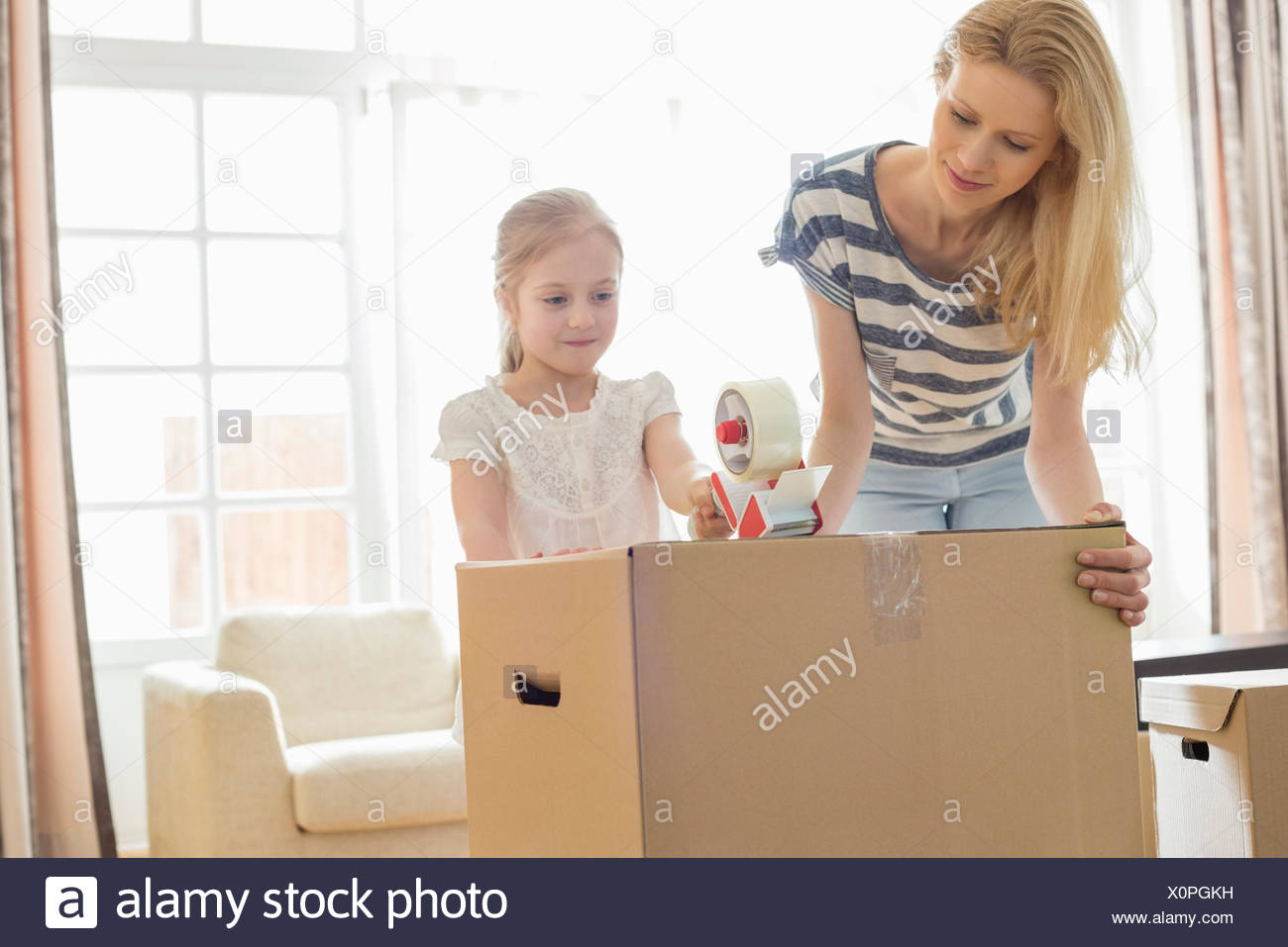 Mother and daughter packing cardboard box at home - Stock Image