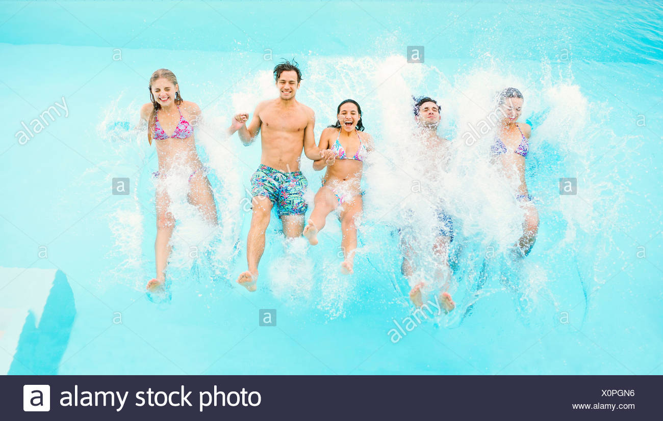 Friends jumping into swimming pool - Stock Image
