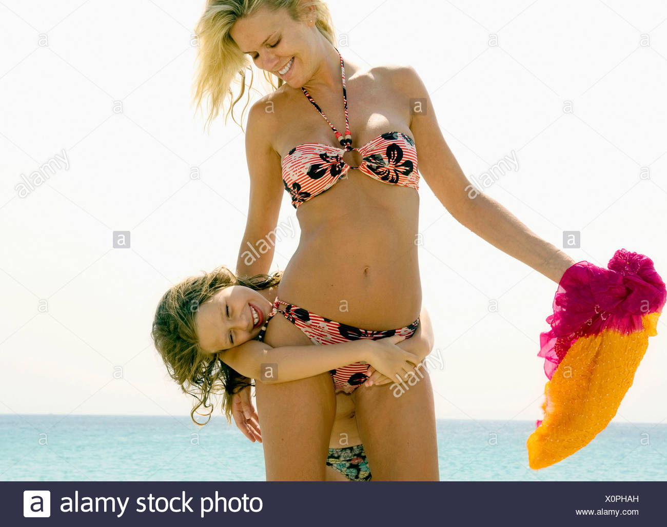 Woman and young girl being playful at the beach smiling. Stock Photo