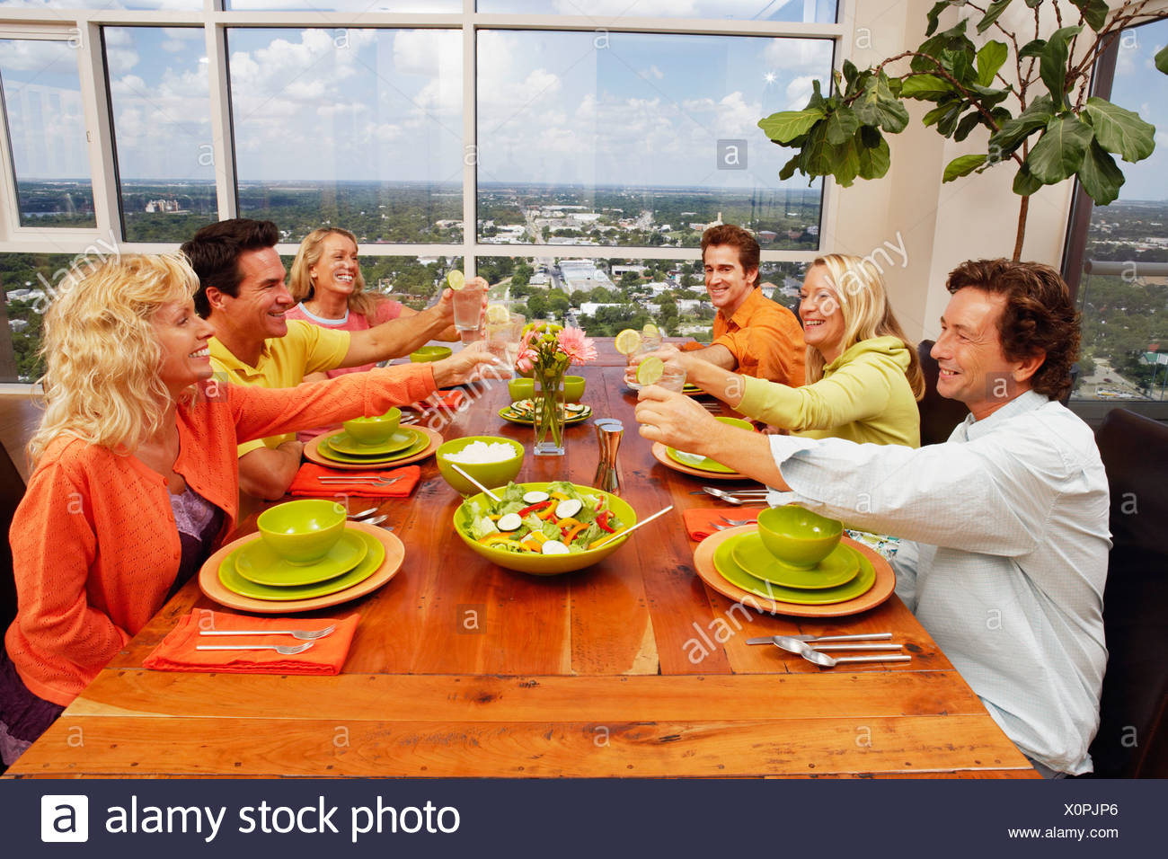 Group of people sitting at the dining table and toasting a drink