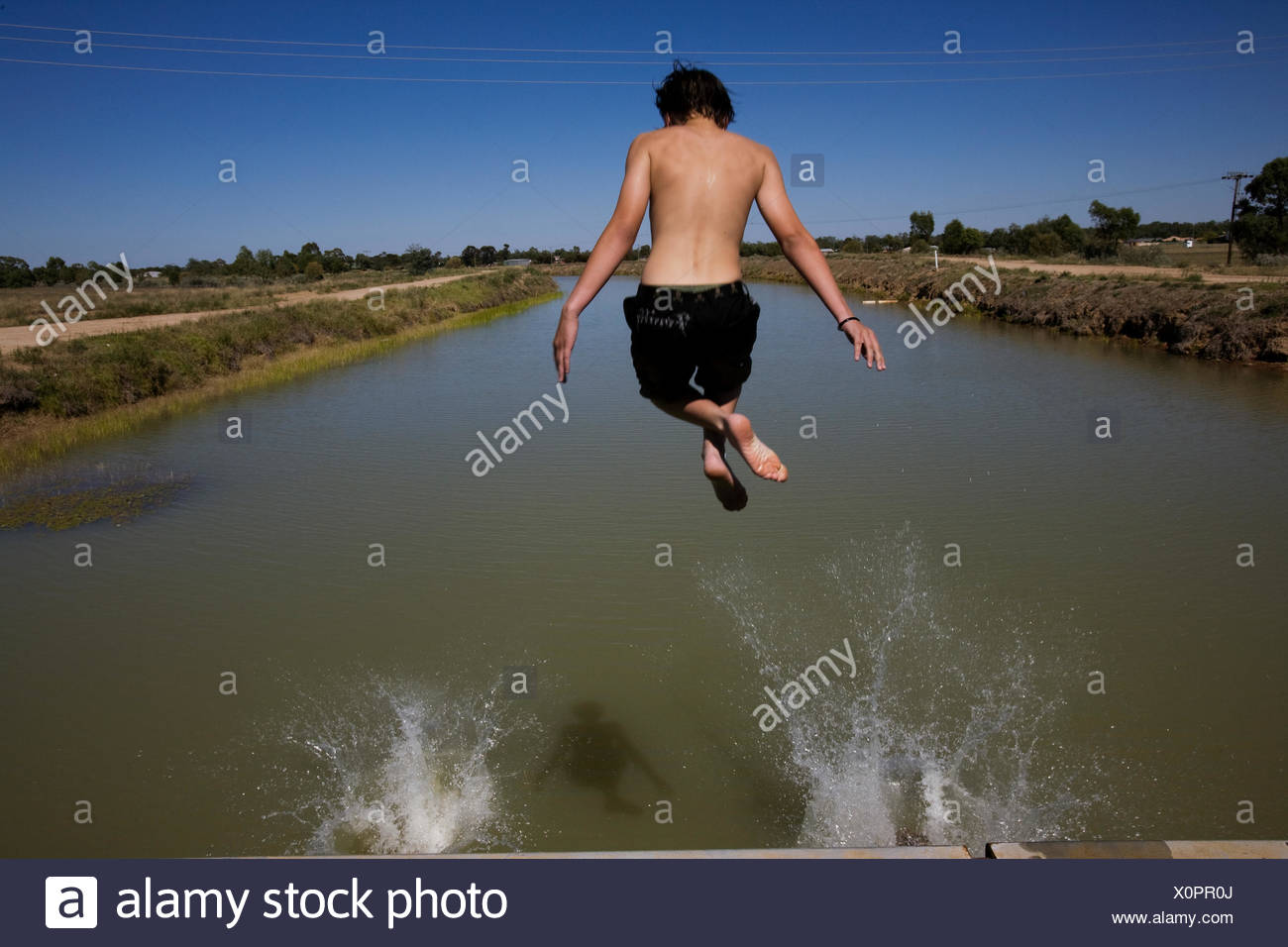 A boy jumps into the Mulwala Canal, the largest irrigation canal in the Murray-Darling Basin. - Stock Image
