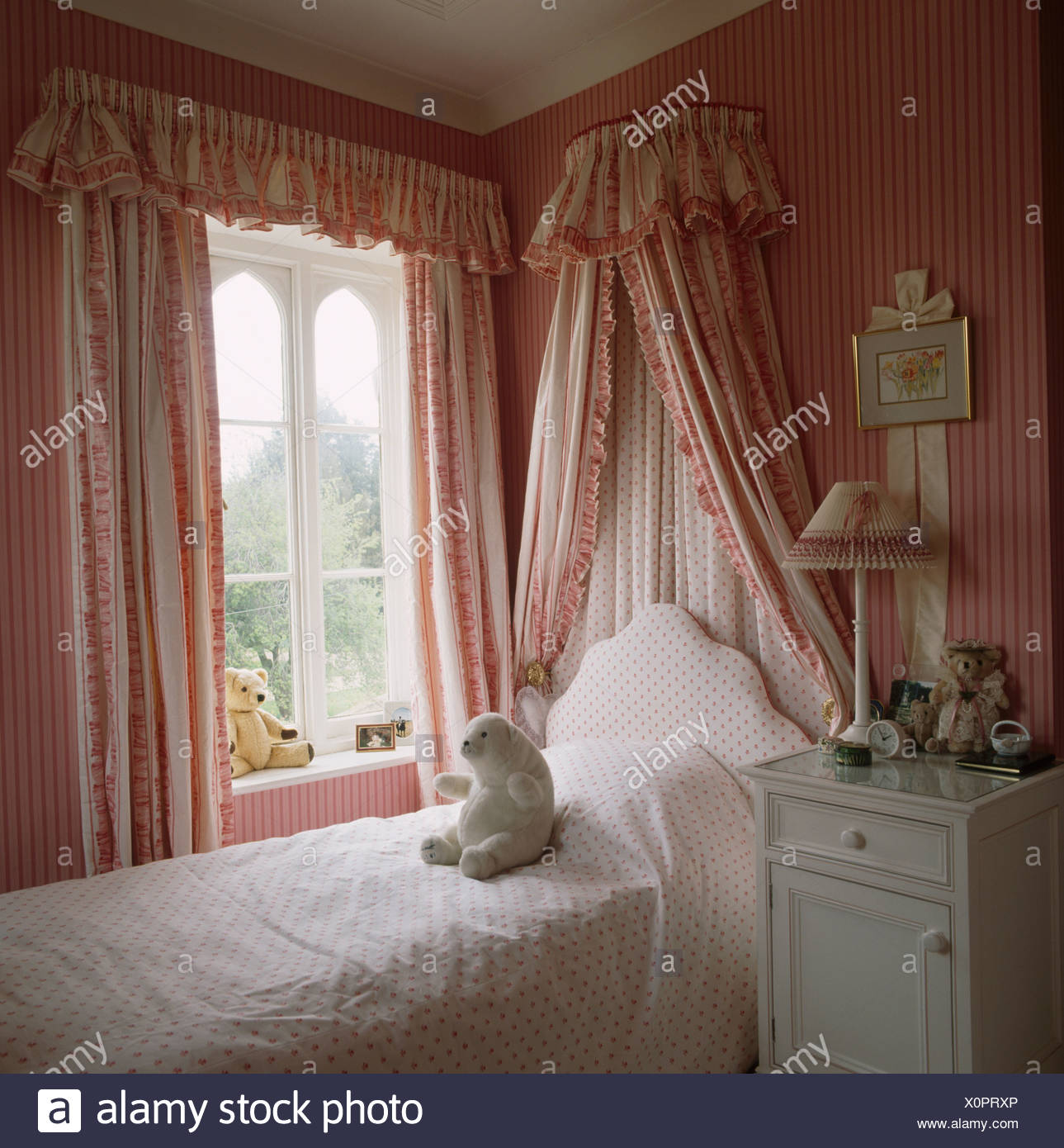 Bed With Coronet And Drapes Beside Window In Childs Bedroom With Pink Striped Wallpaper And Pink Curtains Stock Photo Alamy