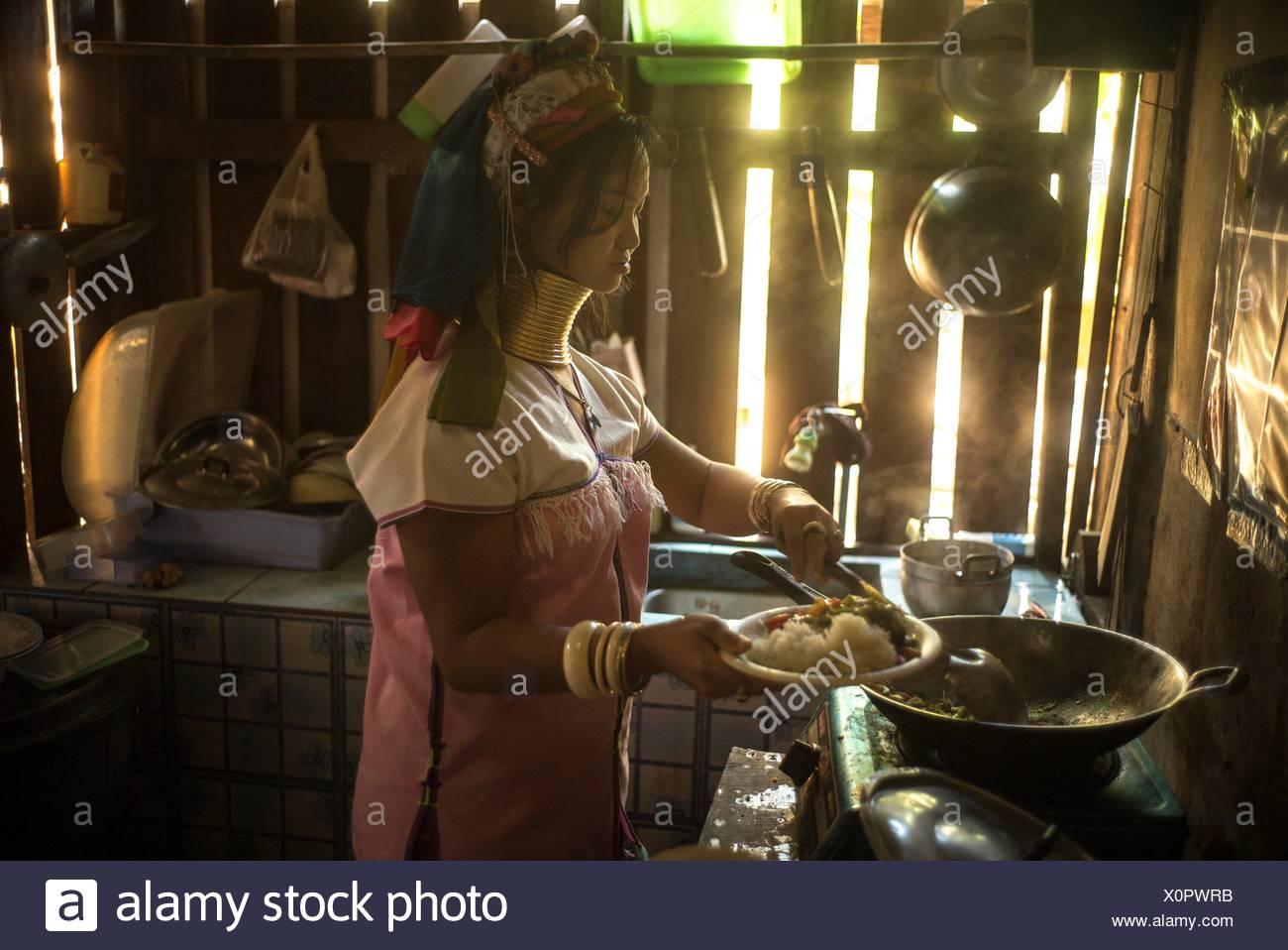 A Karenni woman serves breakfast in her kitchen. - Stock Image