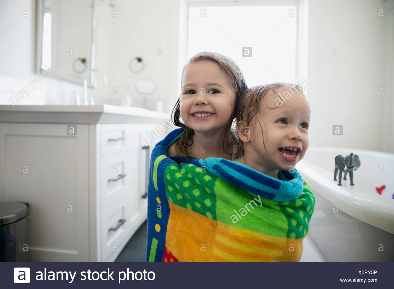 Portrait enthusiastic sisters wrapped a towel bathroom - Stock Image
