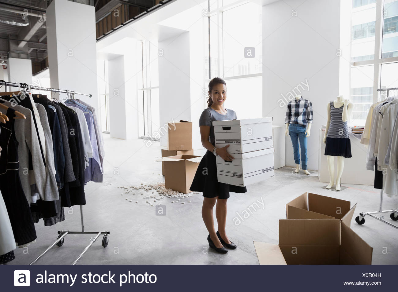 Portrait fashion stylist carrying boxes in studio - Stock Image