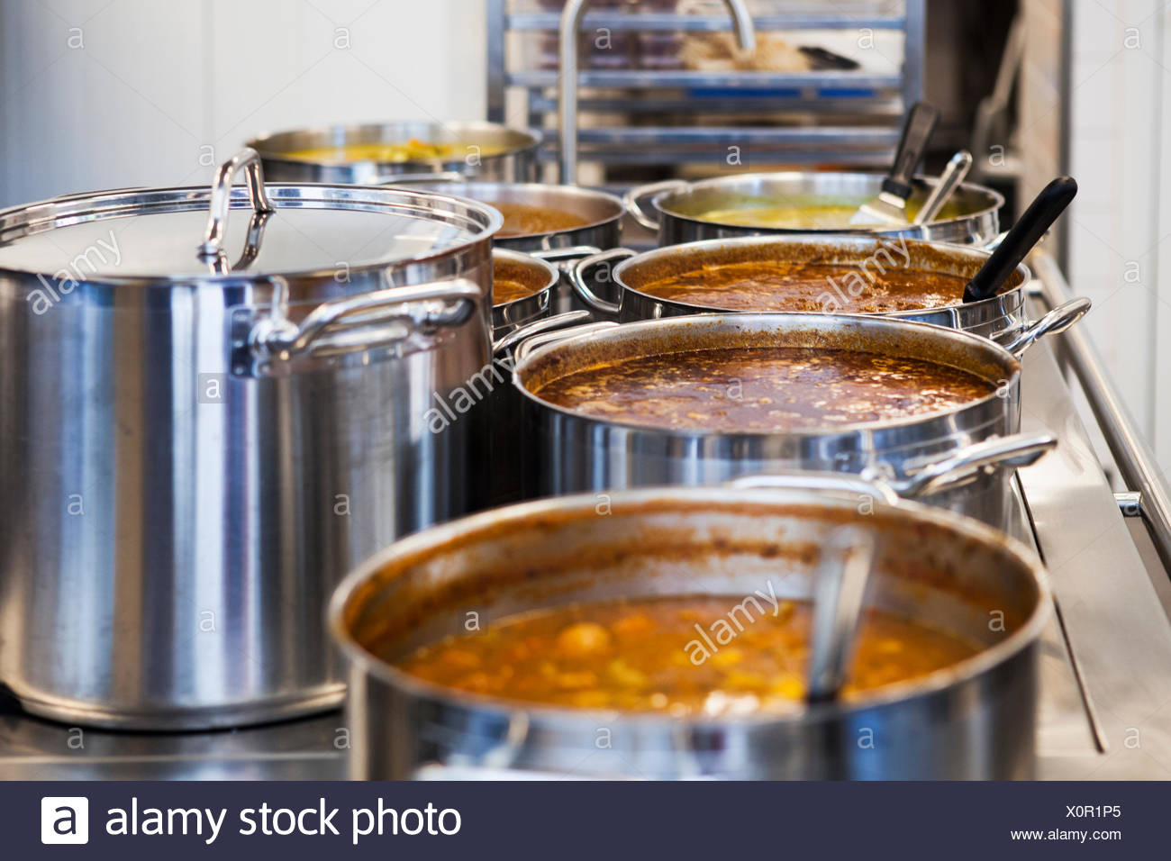 Food in saucepans on table at commercial kitchen - Stock Image