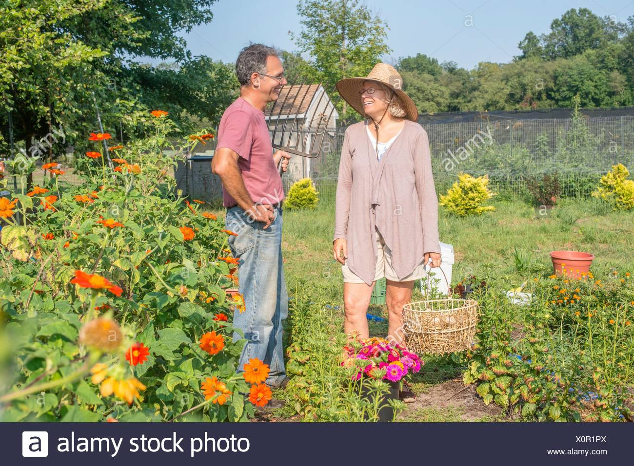 Male and female farmers chatting in garden - Stock Image