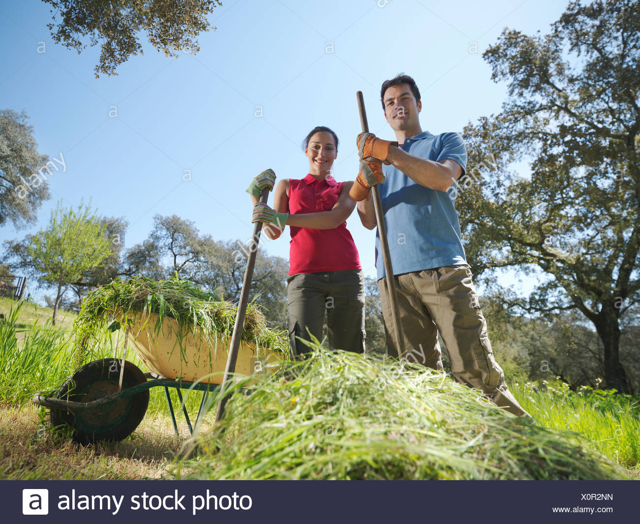 Man and woman in front of hay heap - Stock Image