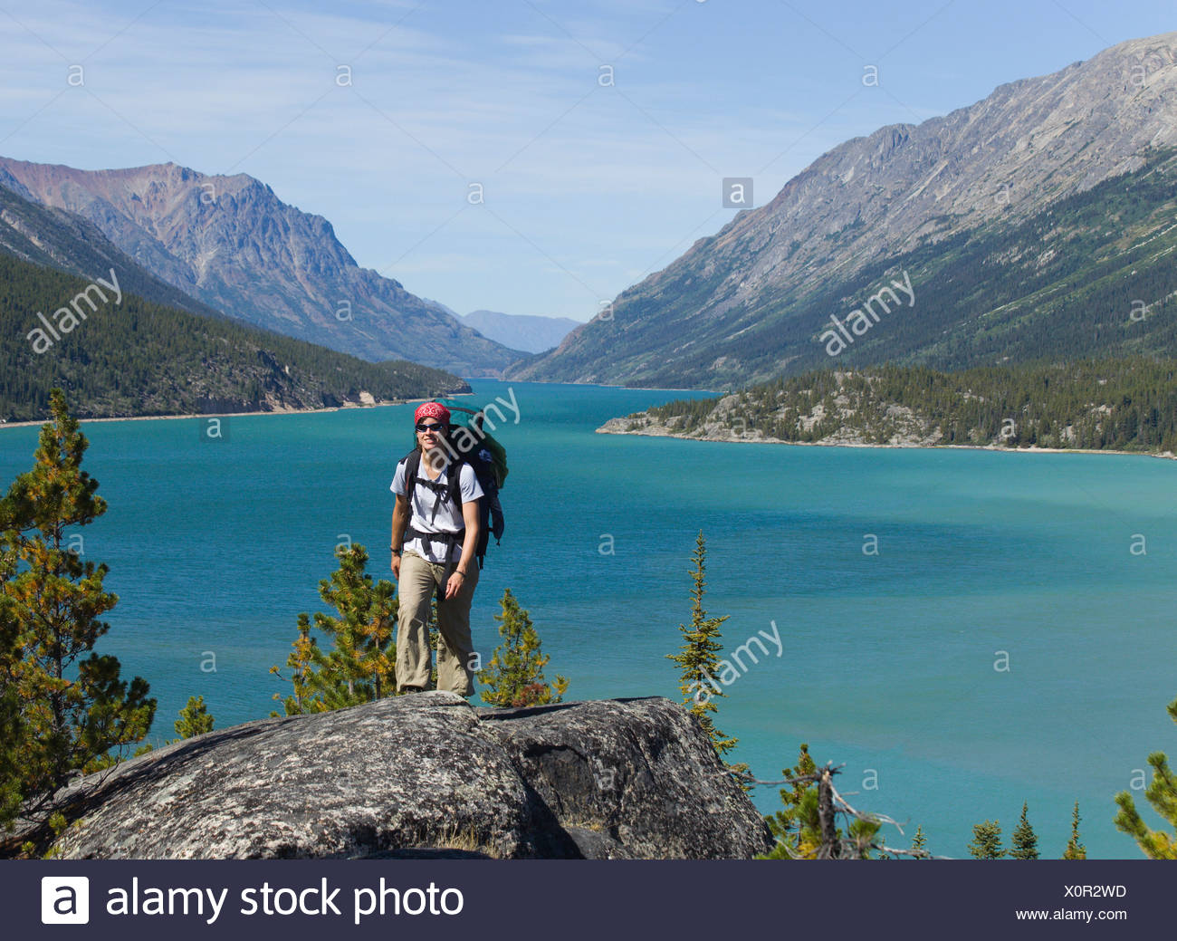 Young woman hiking, backpacking, hiker with backpack, historic Chilkoot Pass, Chilkoot Trail, Lake Bennett behind - Stock Image