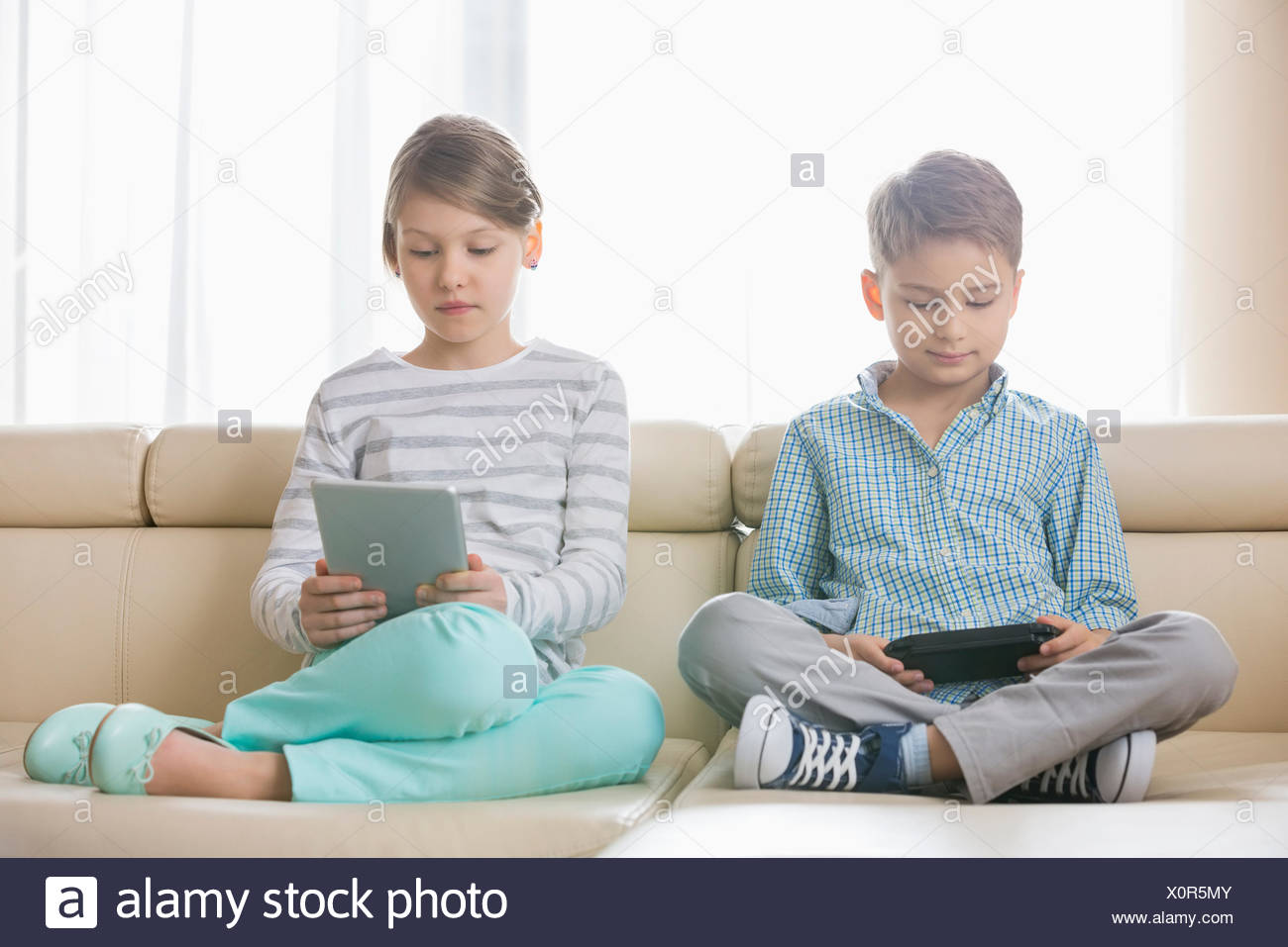 Cute siblings using technologies on sofa at home - Stock Image