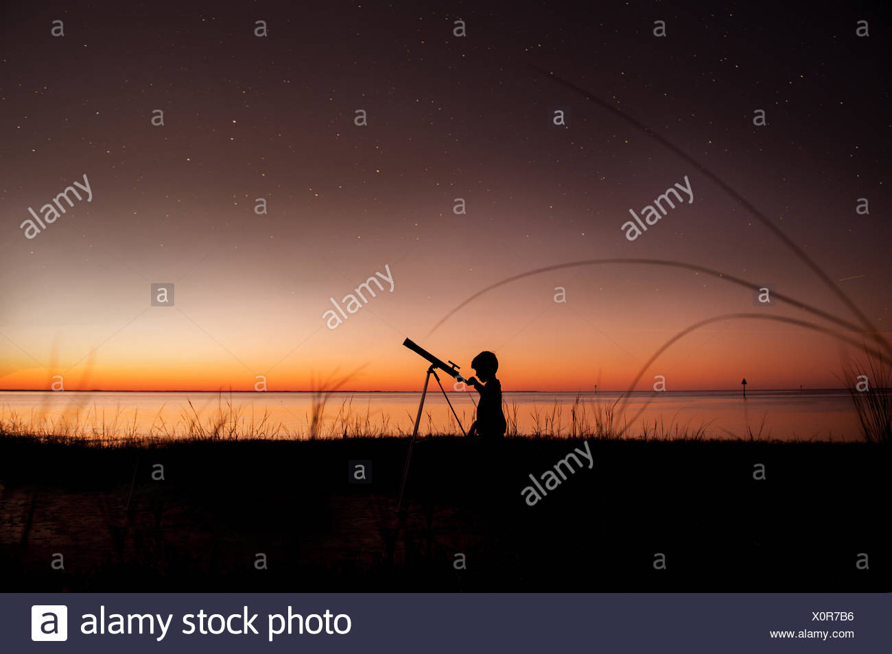 Silhouette of boy looking at stars through telescope - Stock Image