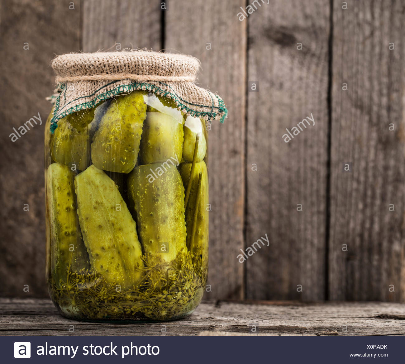 Jar of homemade pickles on a rustic wooden board - Stock Image