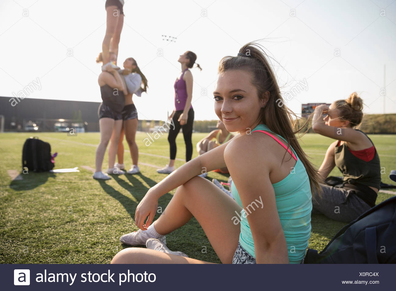 Portrait smiling teenage girl high school cheerleader sitting on sunny football field during practice - Stock Image
