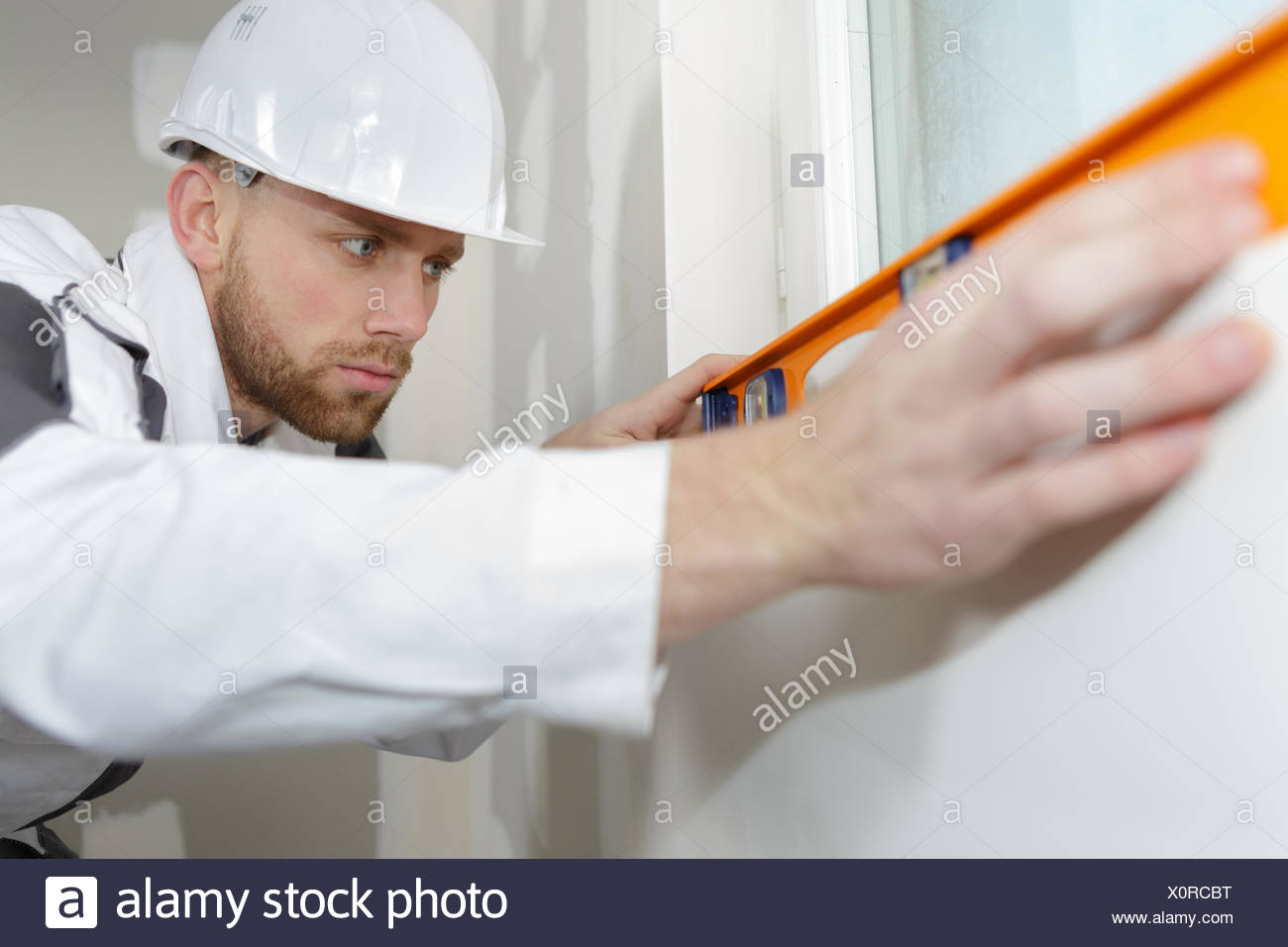 plasterer checking if walls are straight - Stock Image