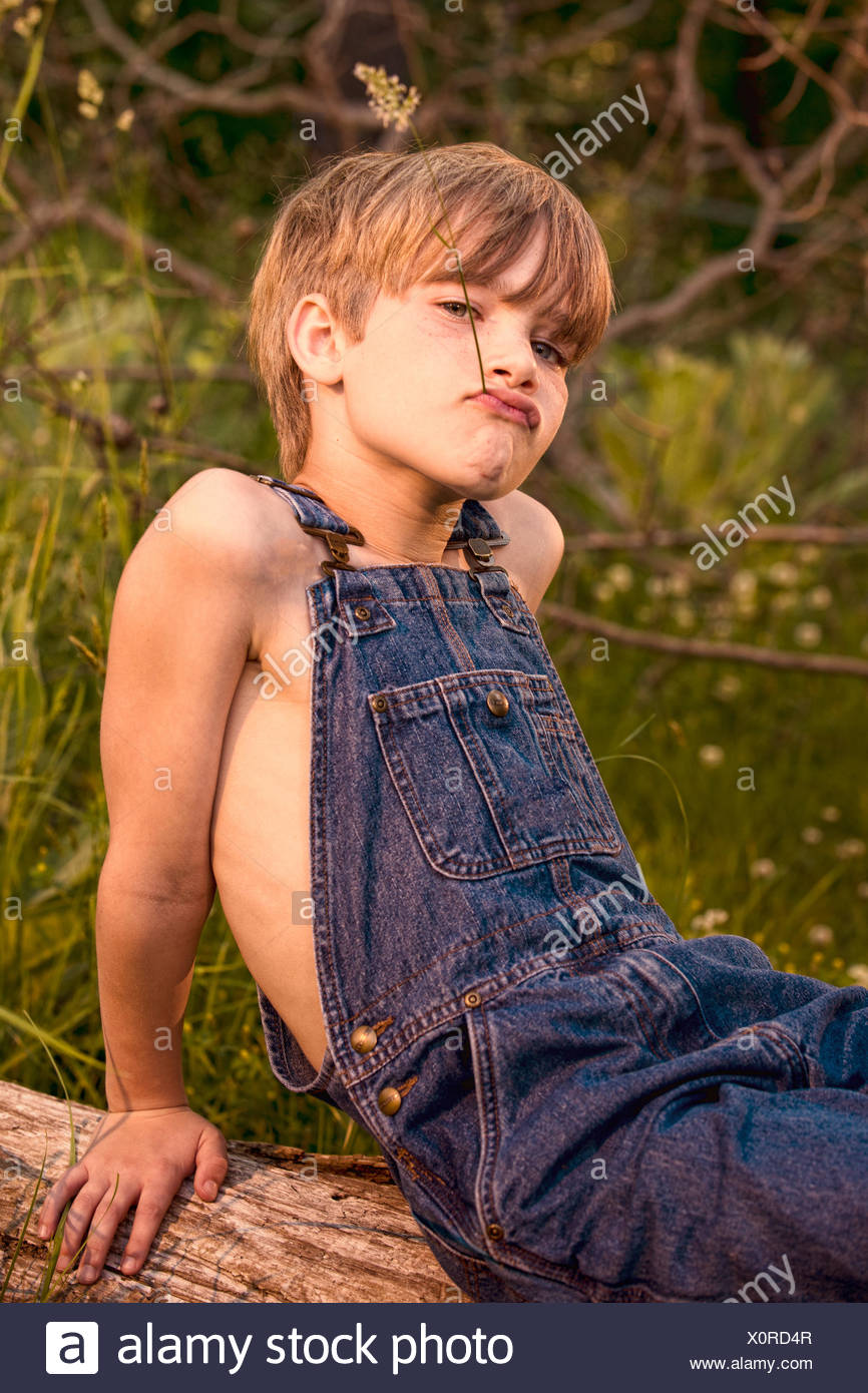 Portrait of a boy sitting on a tree trunk pulling funny faces - Stock Image