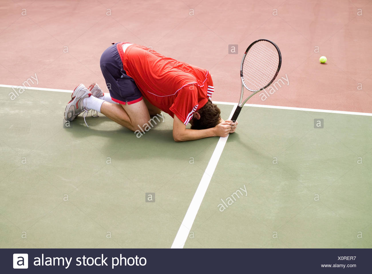 A tennis player crouching on the floor in defeat - Stock Image