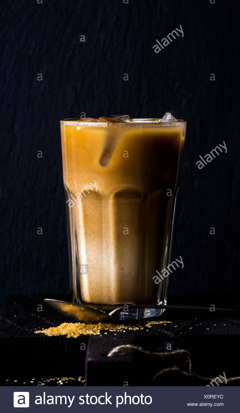 Iced coffee with milk in a tall glass, black background, selective focus - Stock Image