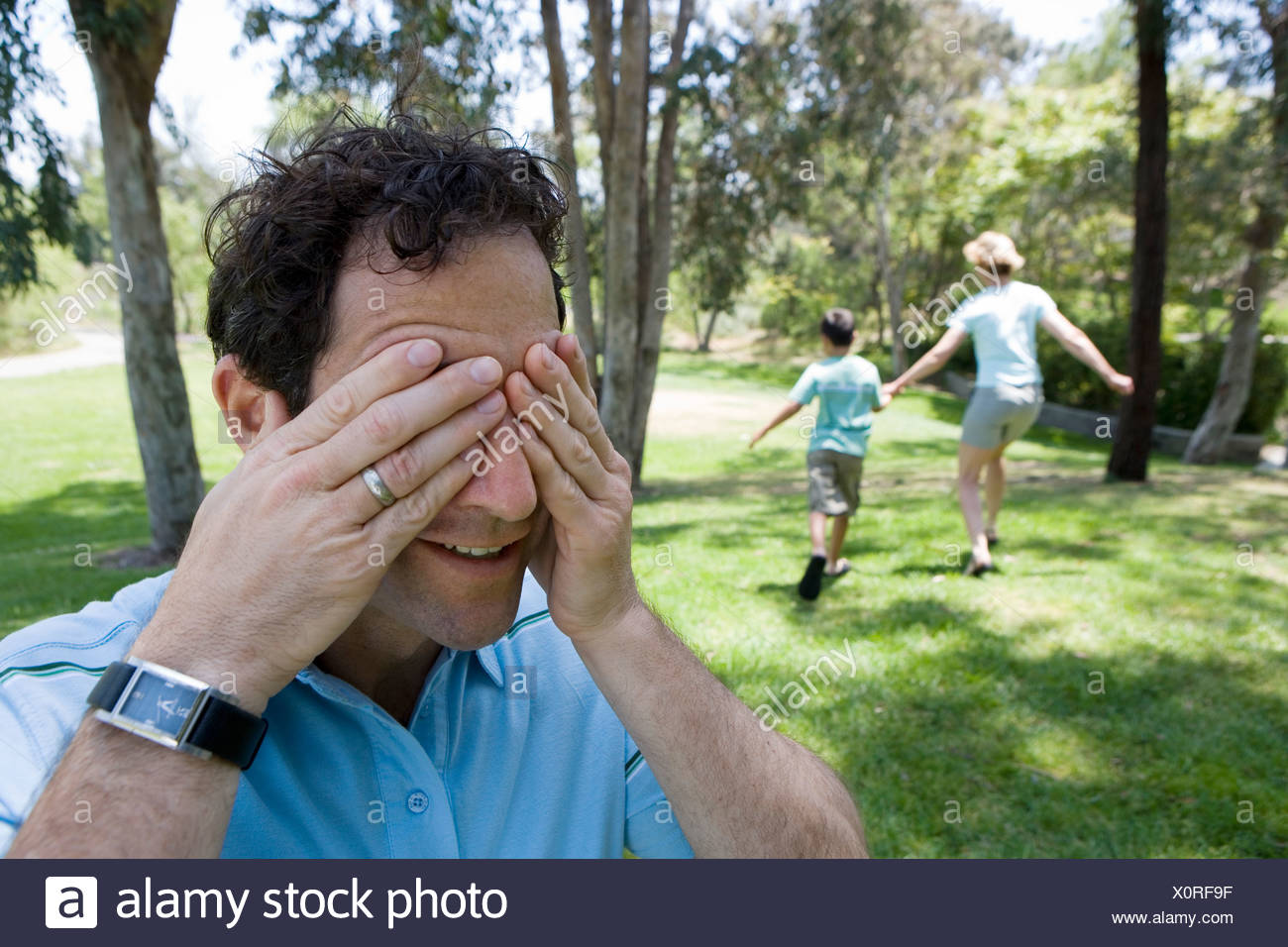 Family playing hide and seek in park boy 9 11 and mother running man covering eyes in foreground - Stock Image