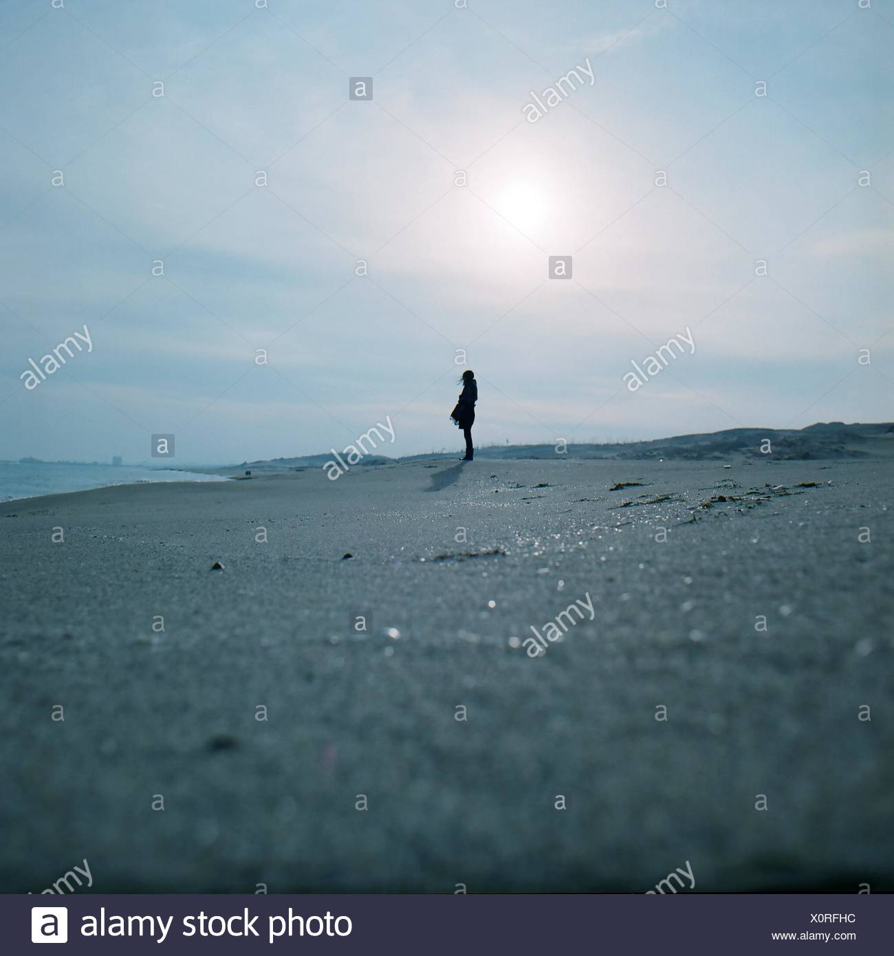 Silhouette Woman Standing On Snowy Field Against Sky - Stock Image
