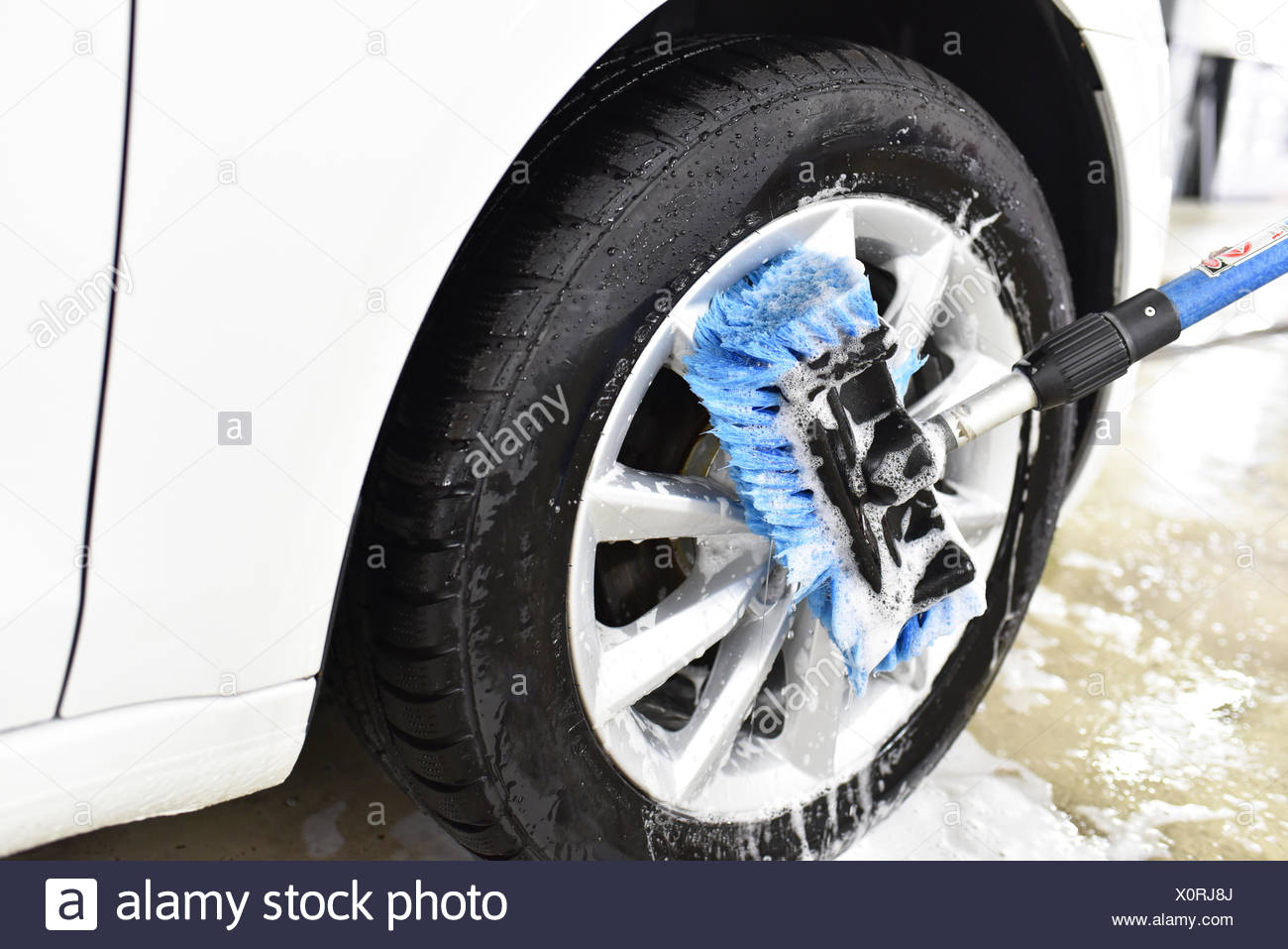 Car cleaning, cleaning the alloy wheel - Stock Image