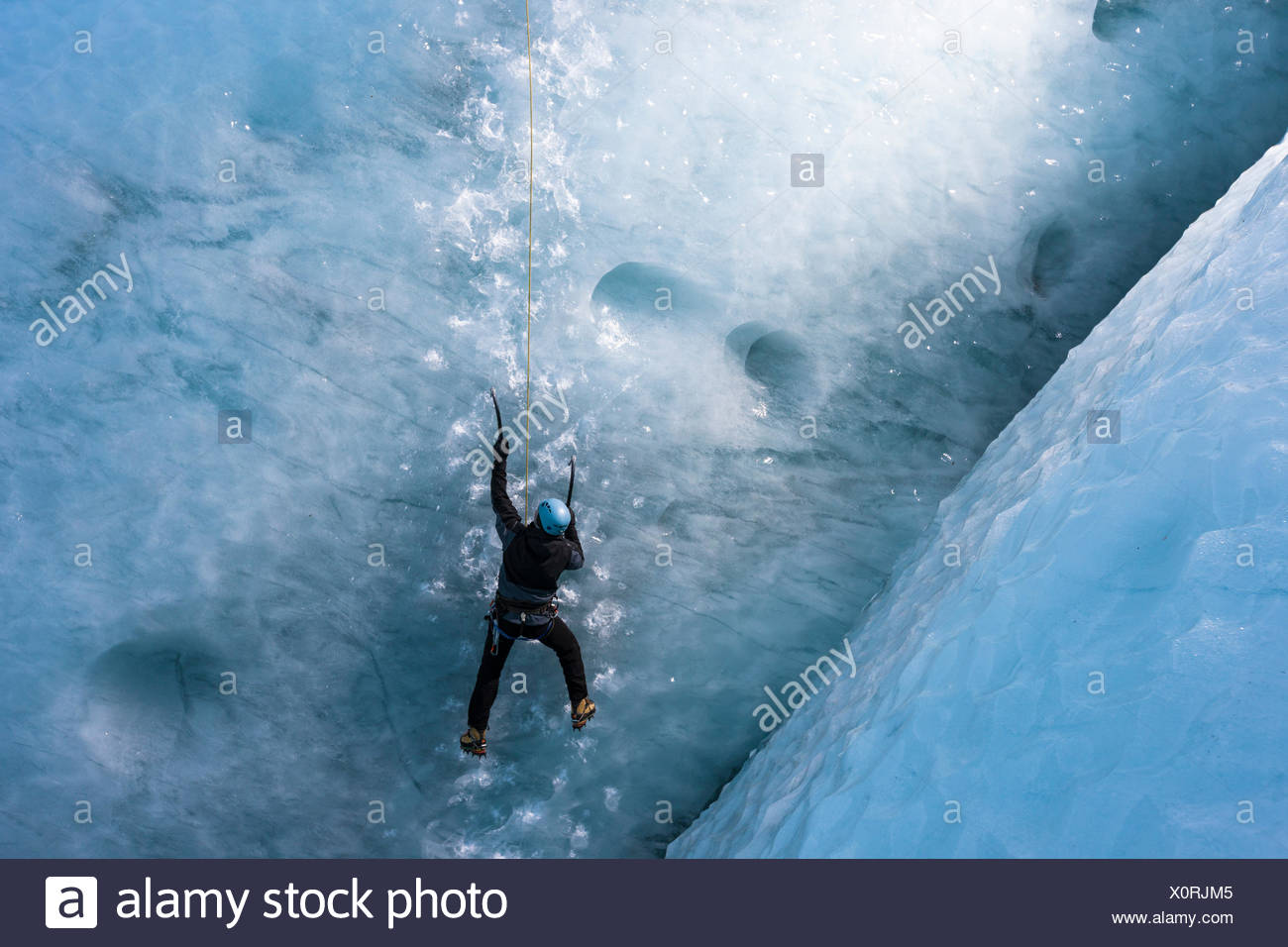 Man climbing vertical glacier ice wall - Stock Image