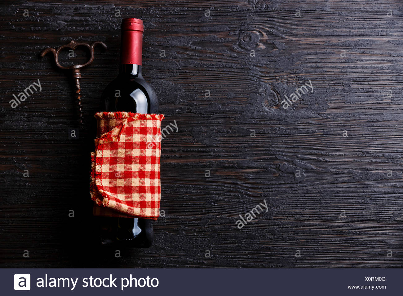 Wine bottle and corkscrew on Black Burned wooden background copy space - Stock Image