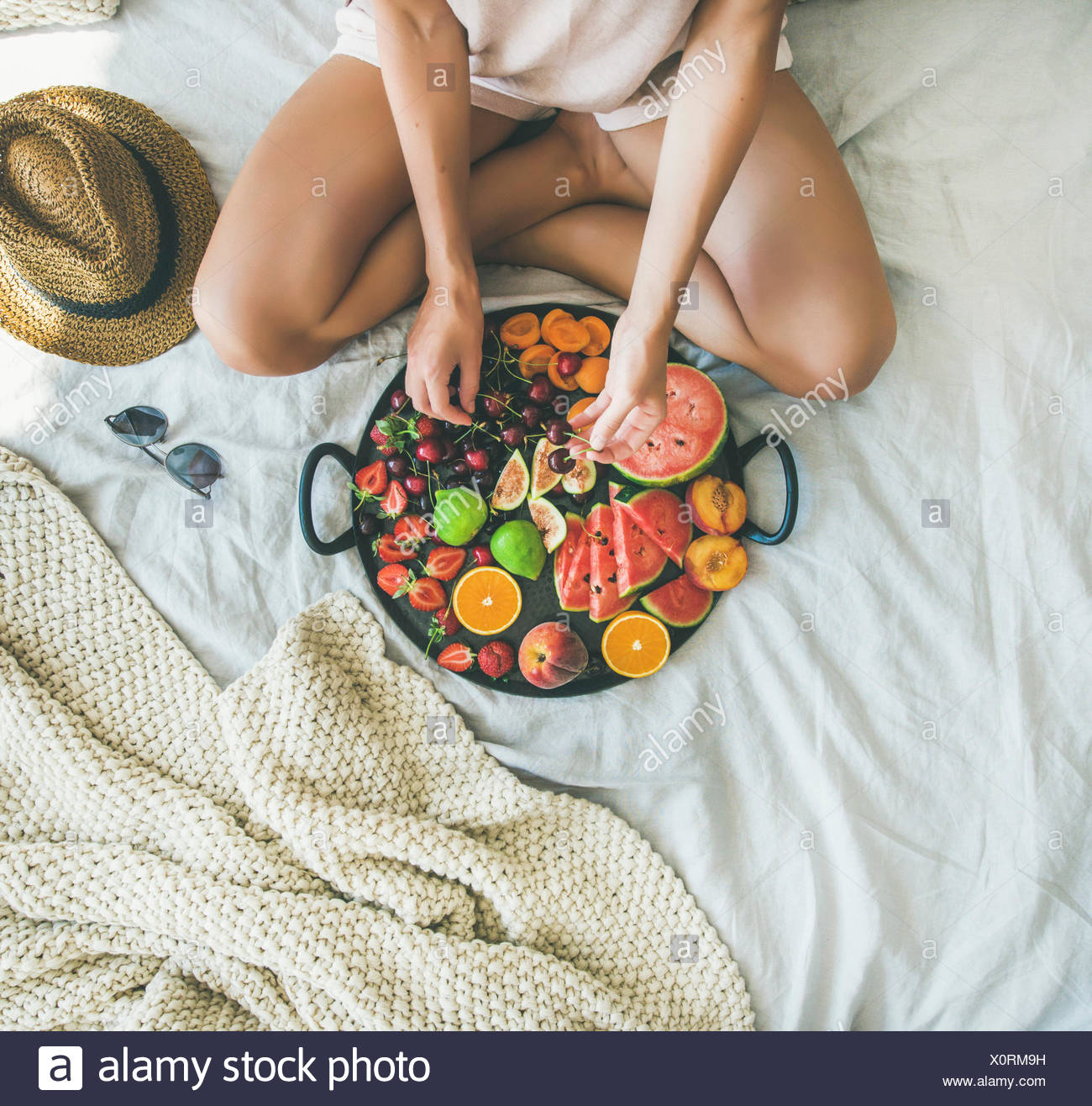 Summer healthy raw vegan clean eating breakfast in bed concept. Young girl wearing pastel colored home clothes taking cherries from tray full of fresh - Stock Image