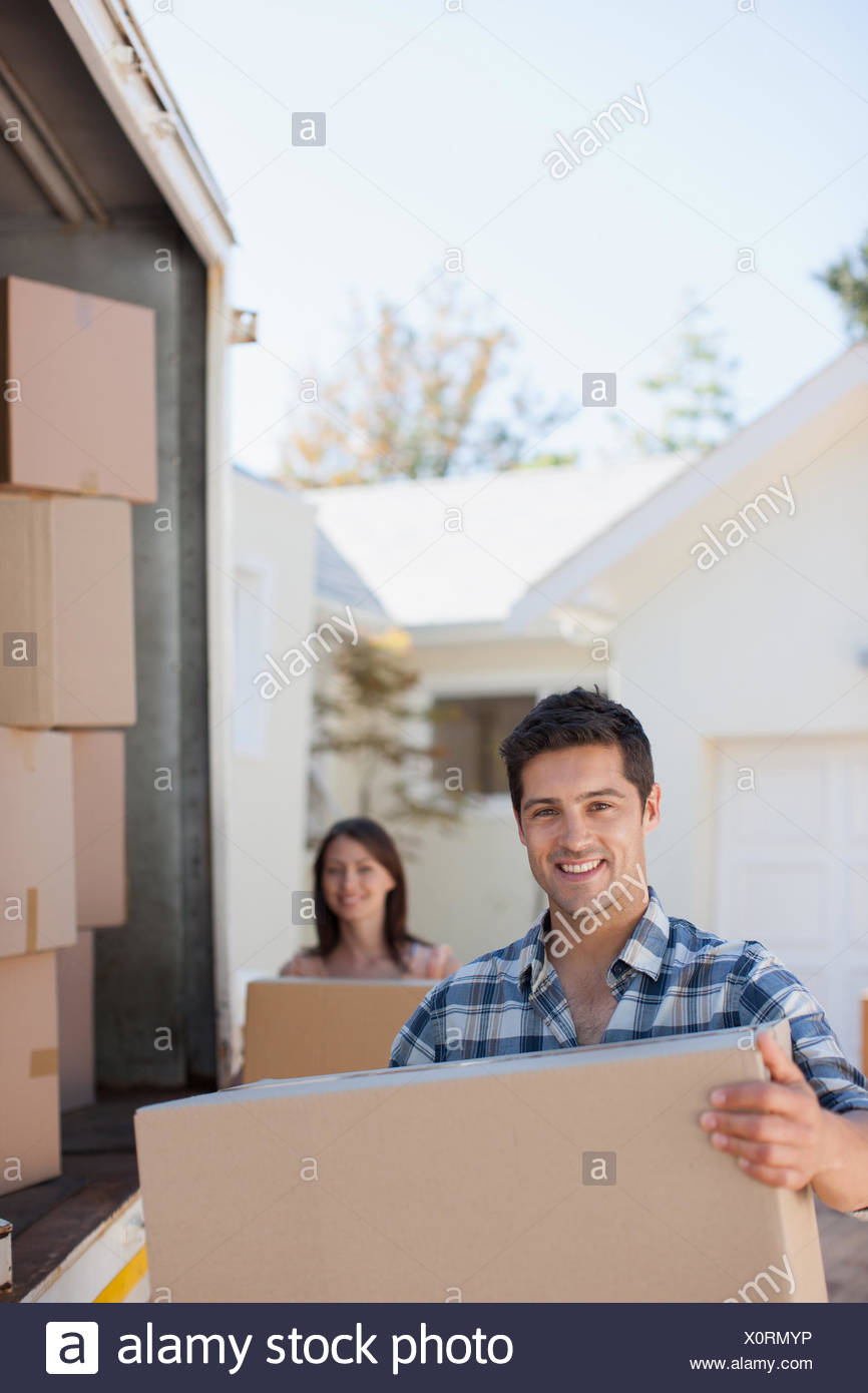 Couple unloading boxes from moving van - Stock Image