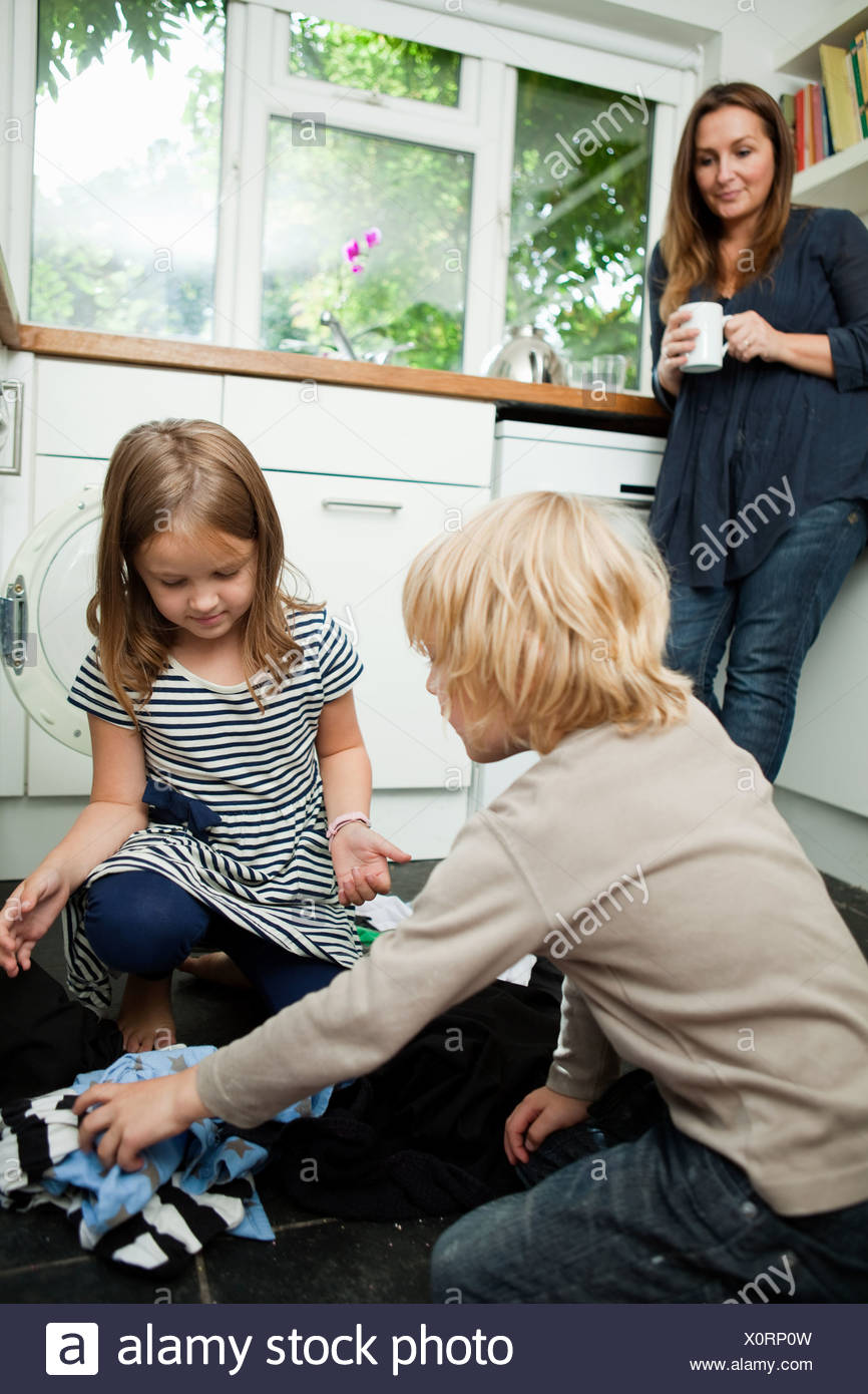 Mid adult woman watching children sort laundry - Stock Image