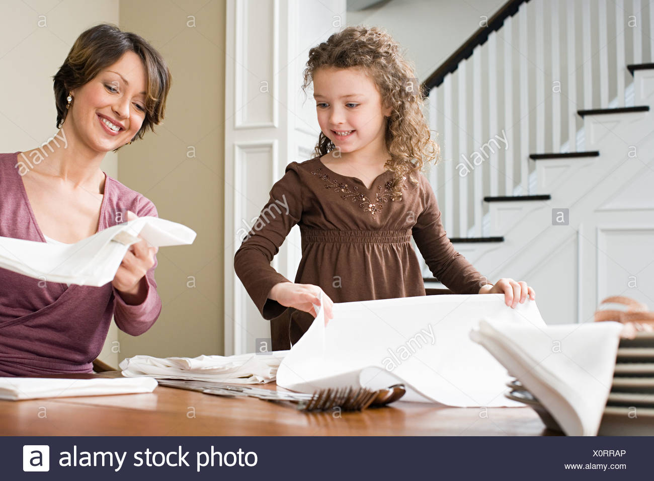 Mother and daughter folding napkins - Stock Image