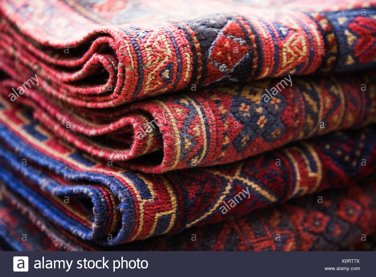 Rugs stacked in market stall - Stock Image