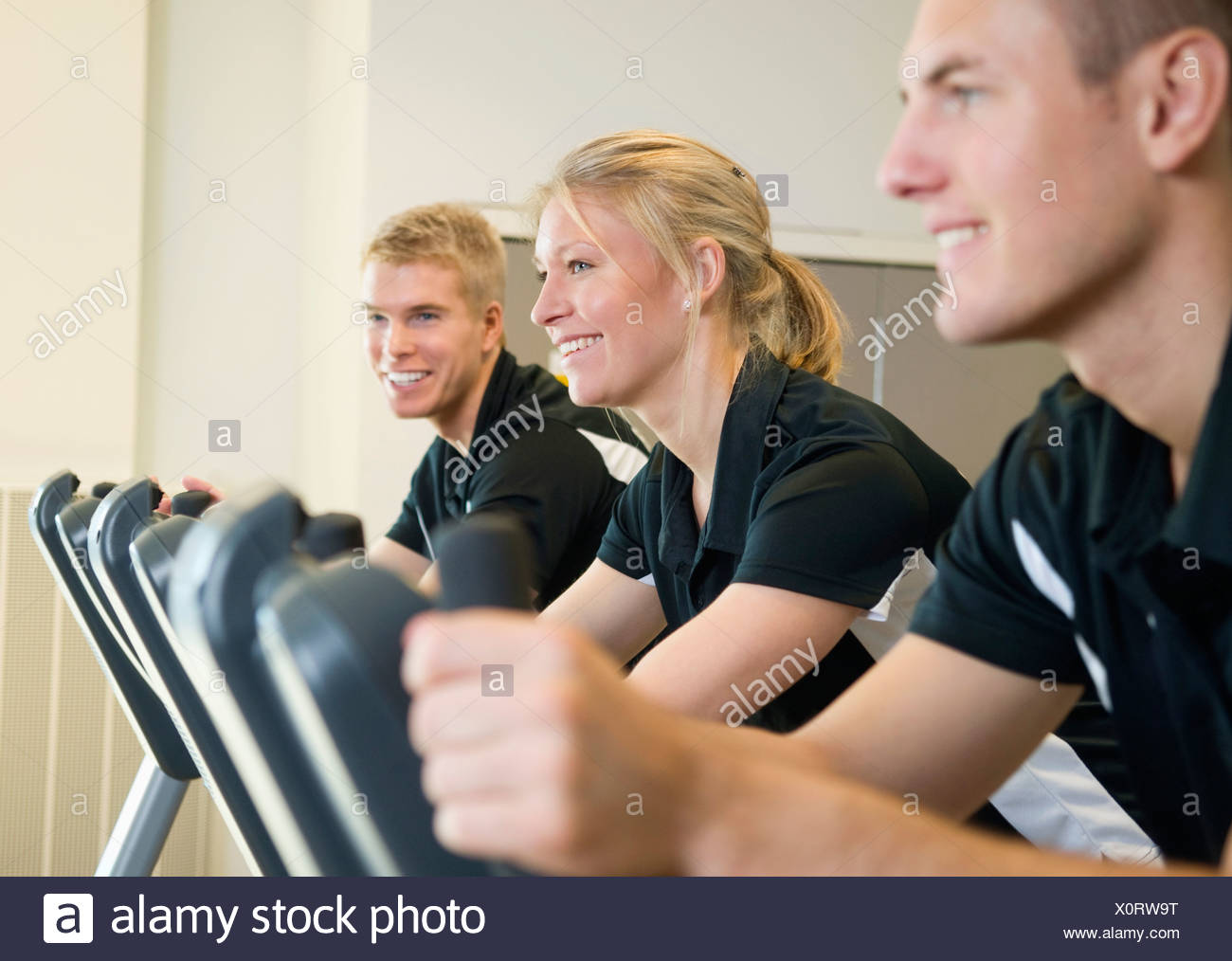 Three smiling people working out - Stock Image